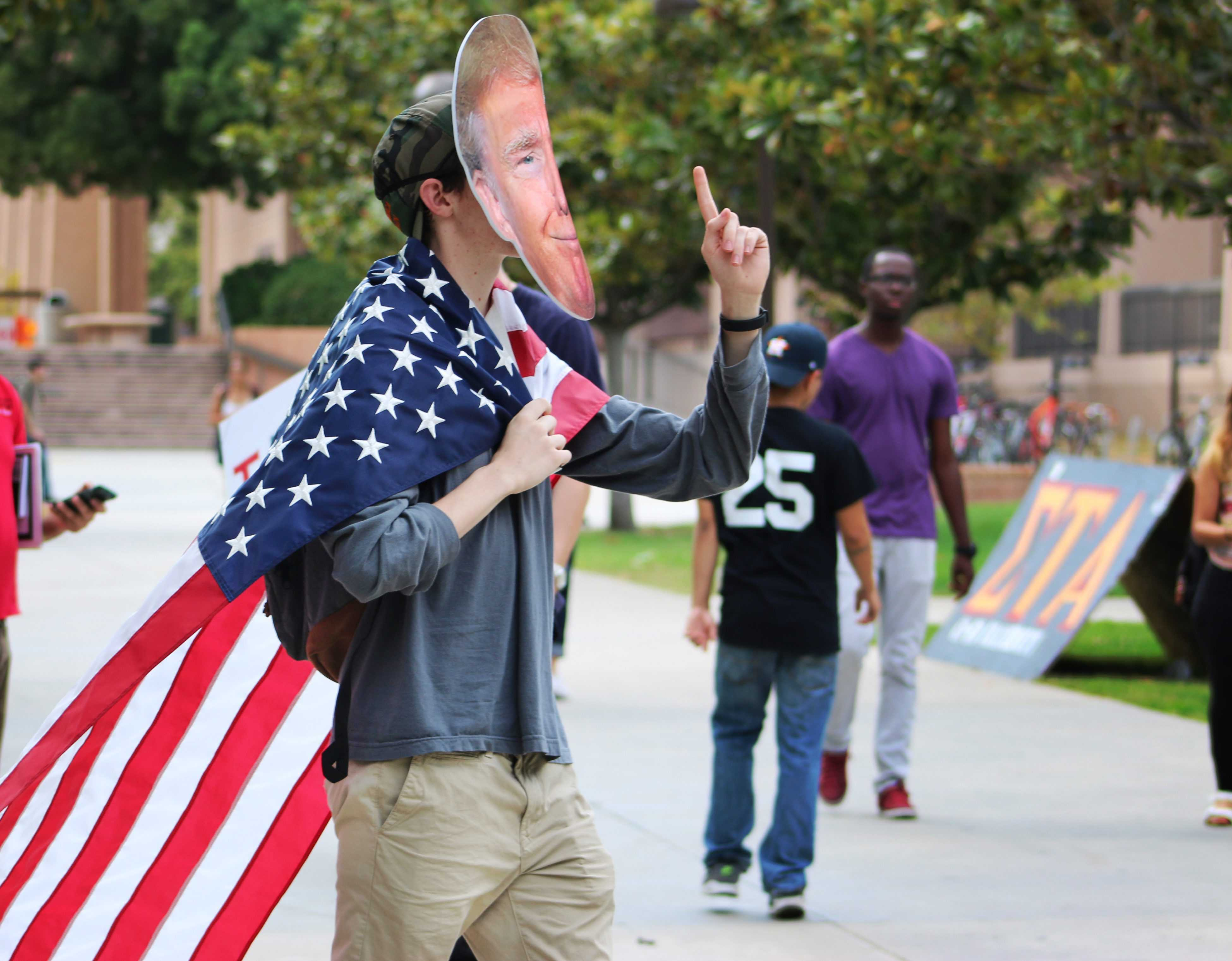 man wears donald trump mask and american flag