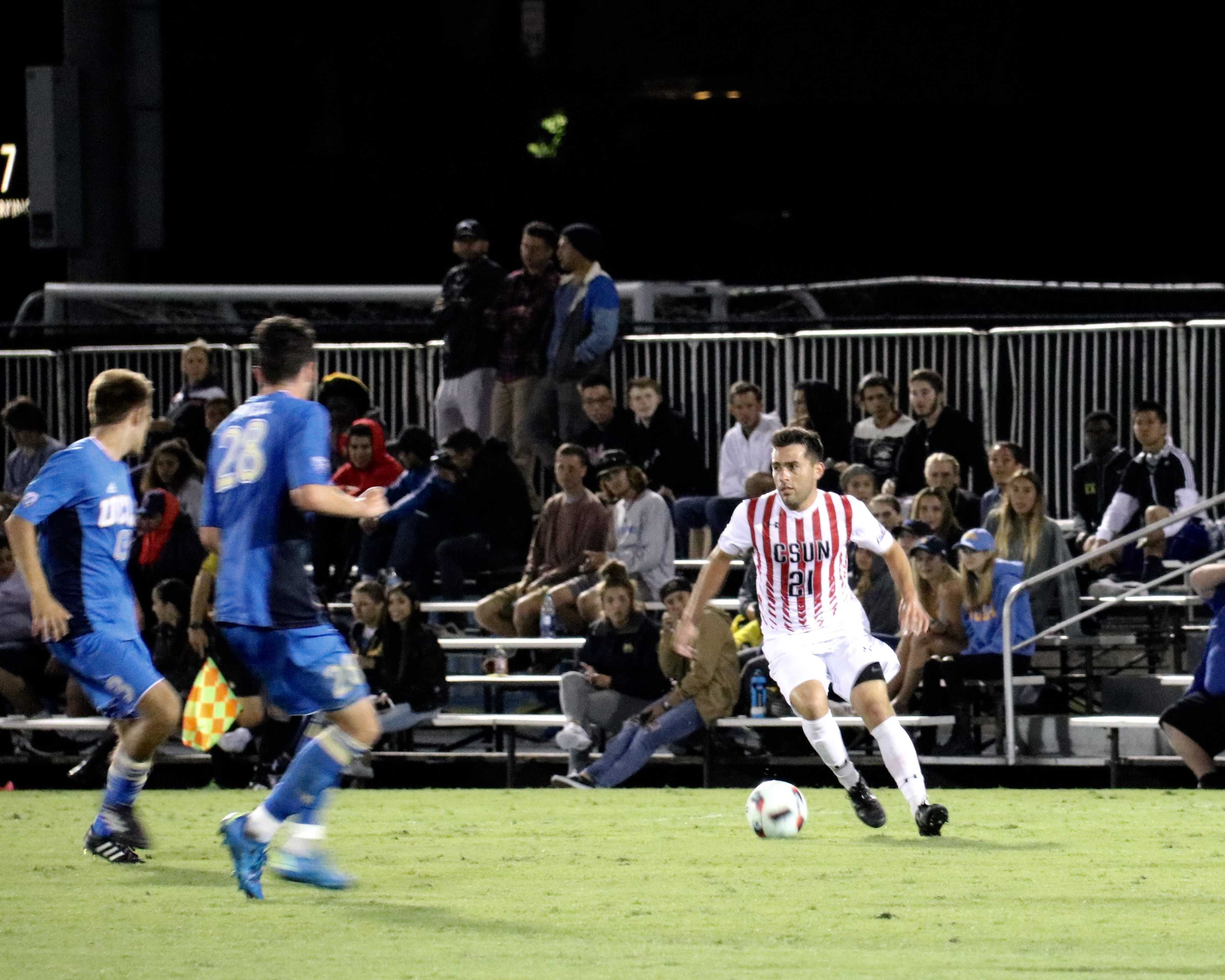 Senior Richard Martinez dribbles the ball away from the UCLA Bruins. Photo credit: Kendall Faulkner