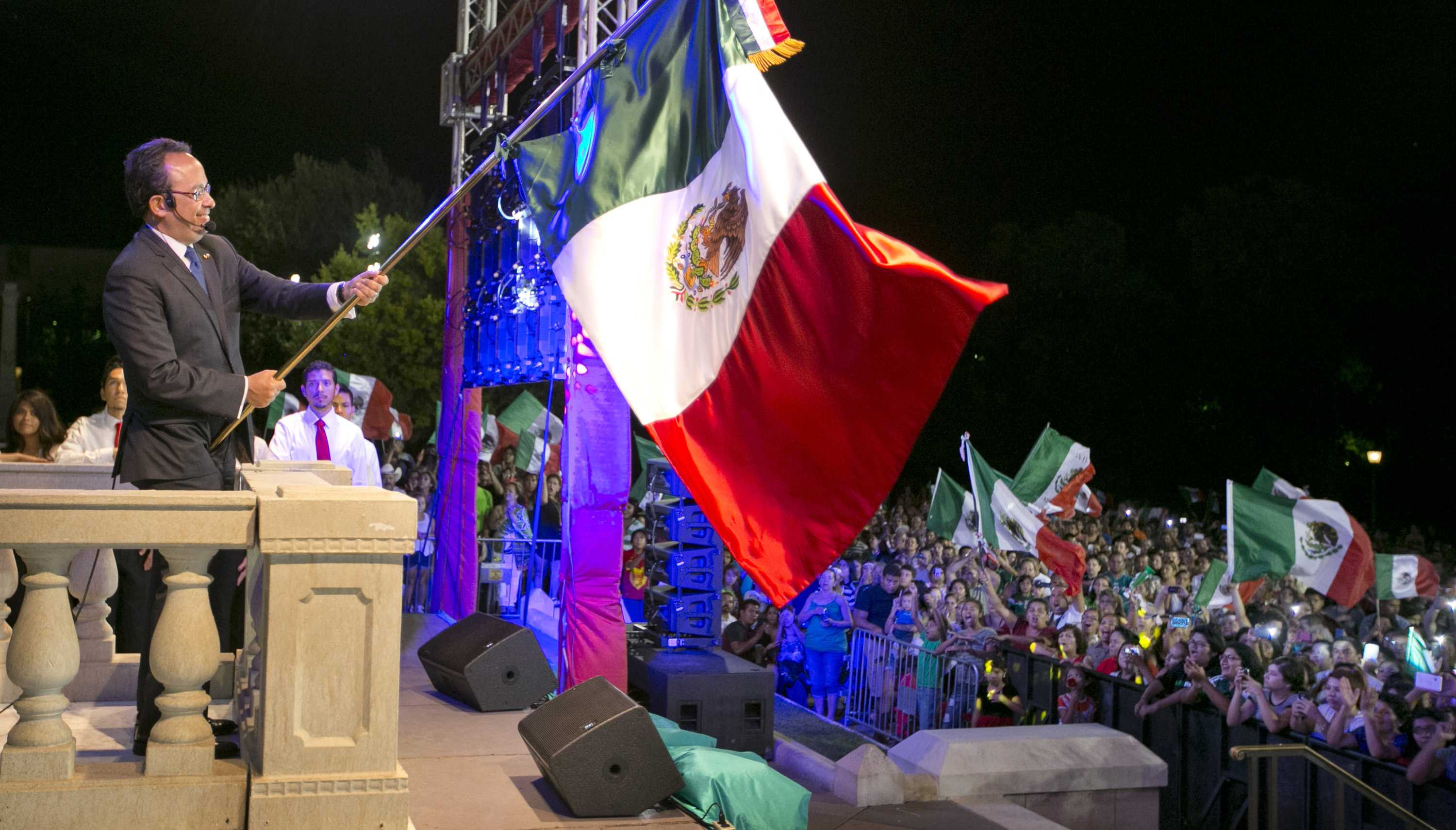 man waves mexican flag over crowd