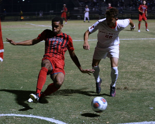 Fullerton soccer player tries to steal ball from CSUN player