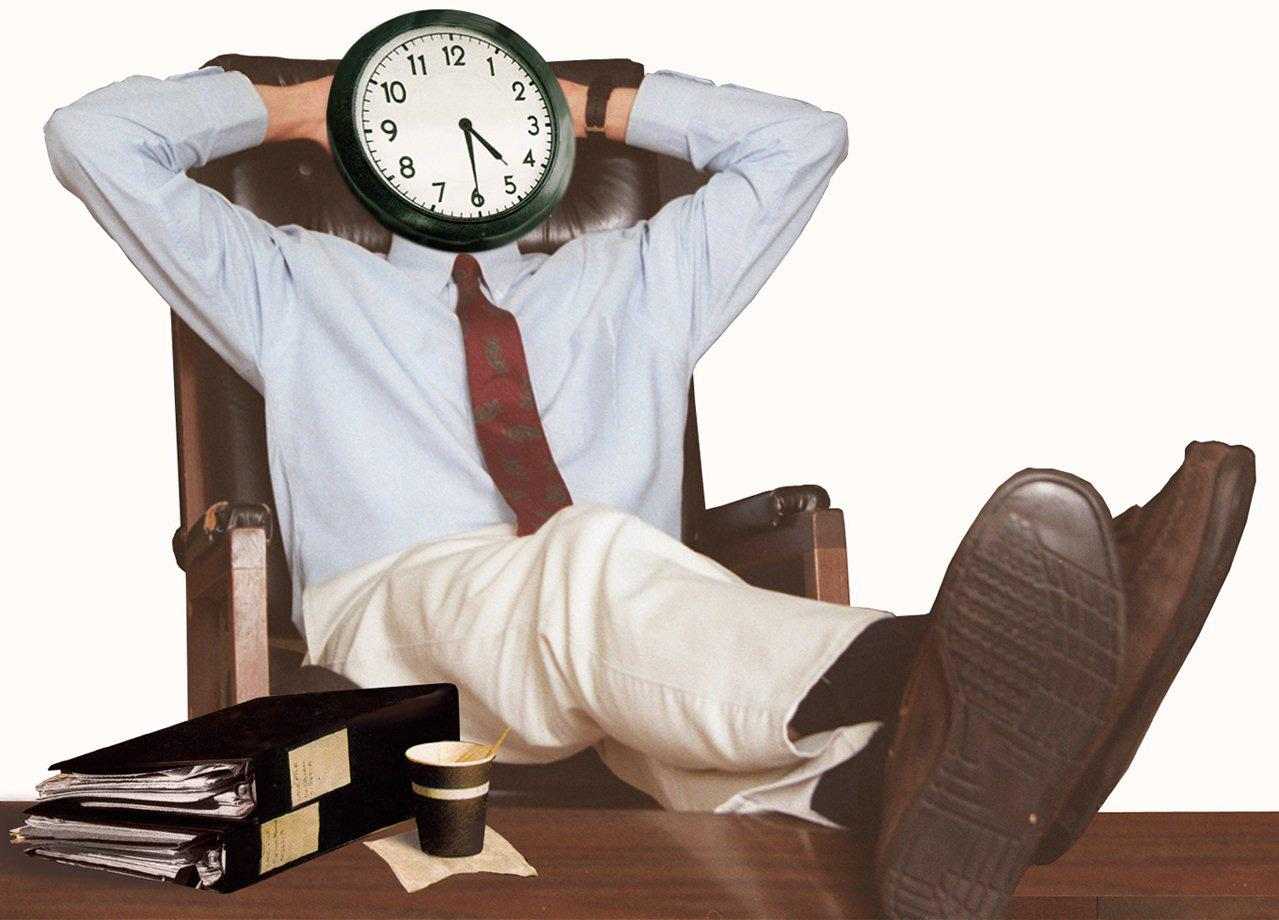 Photo shows man with his feet up on a desk with a clock for a face
