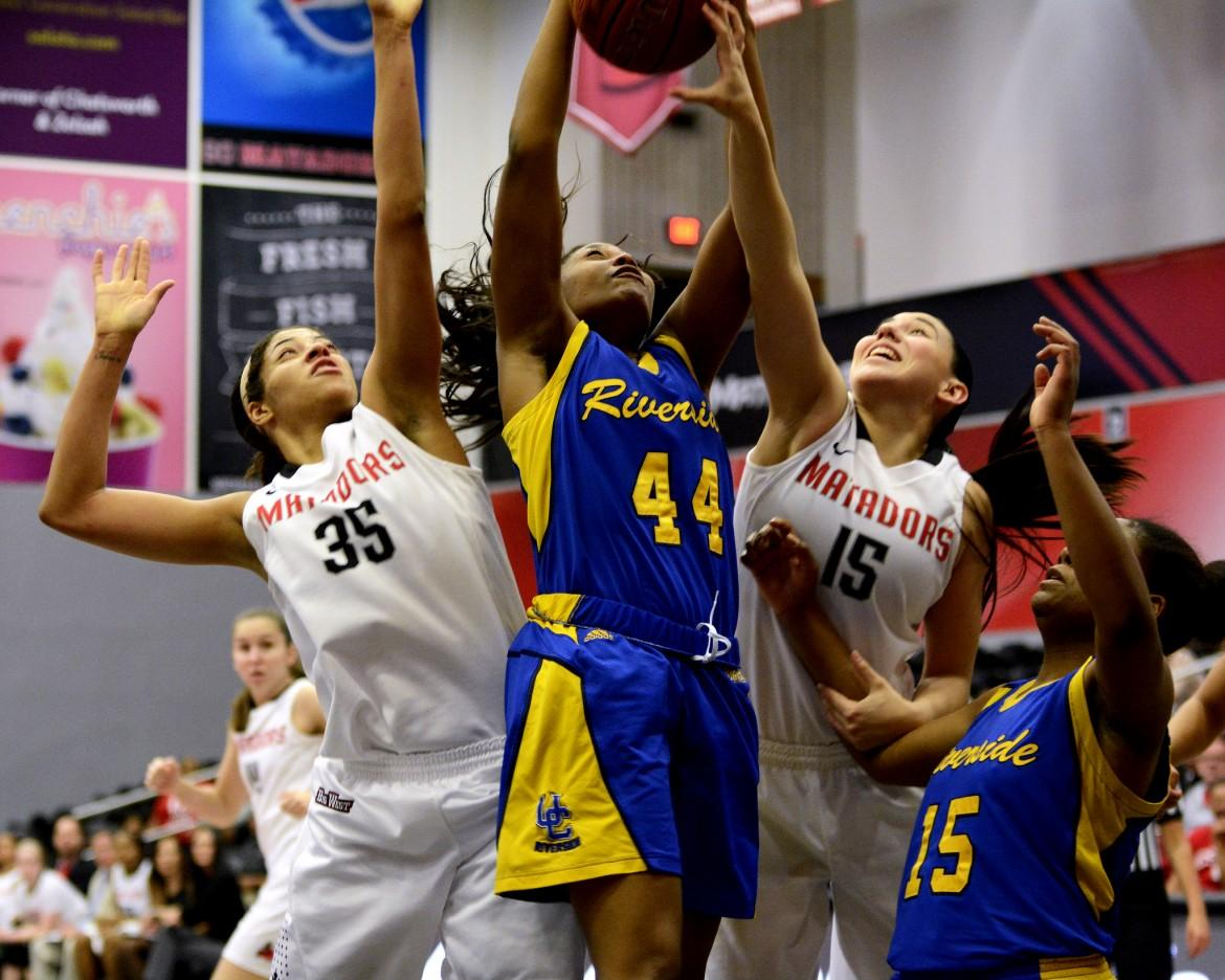 Oppsoing basketball player shoots for the hoop while CSUN players try to block her
