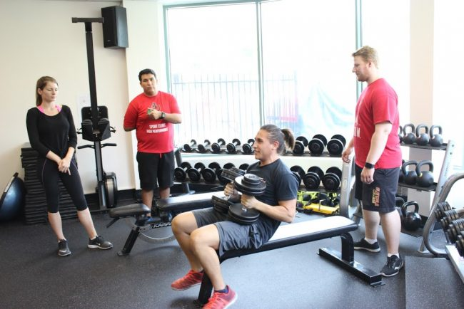 CSUN Rugby fly-half Jordan Rhoades lifting weights as strength and conditioning interns monitor his performance. Photo credit: Robert Spallone