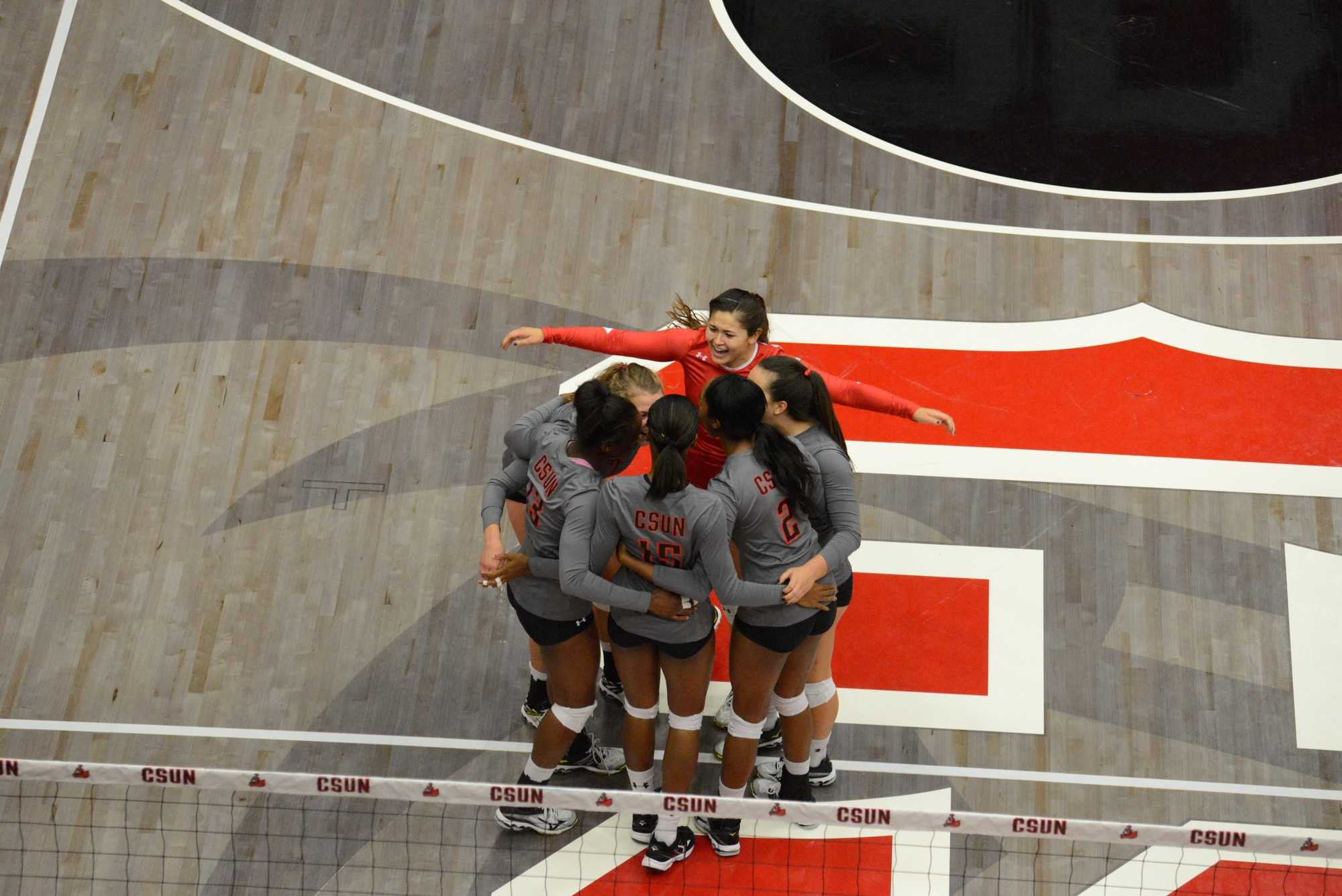 CSUN women's volleyball huddles together during a game