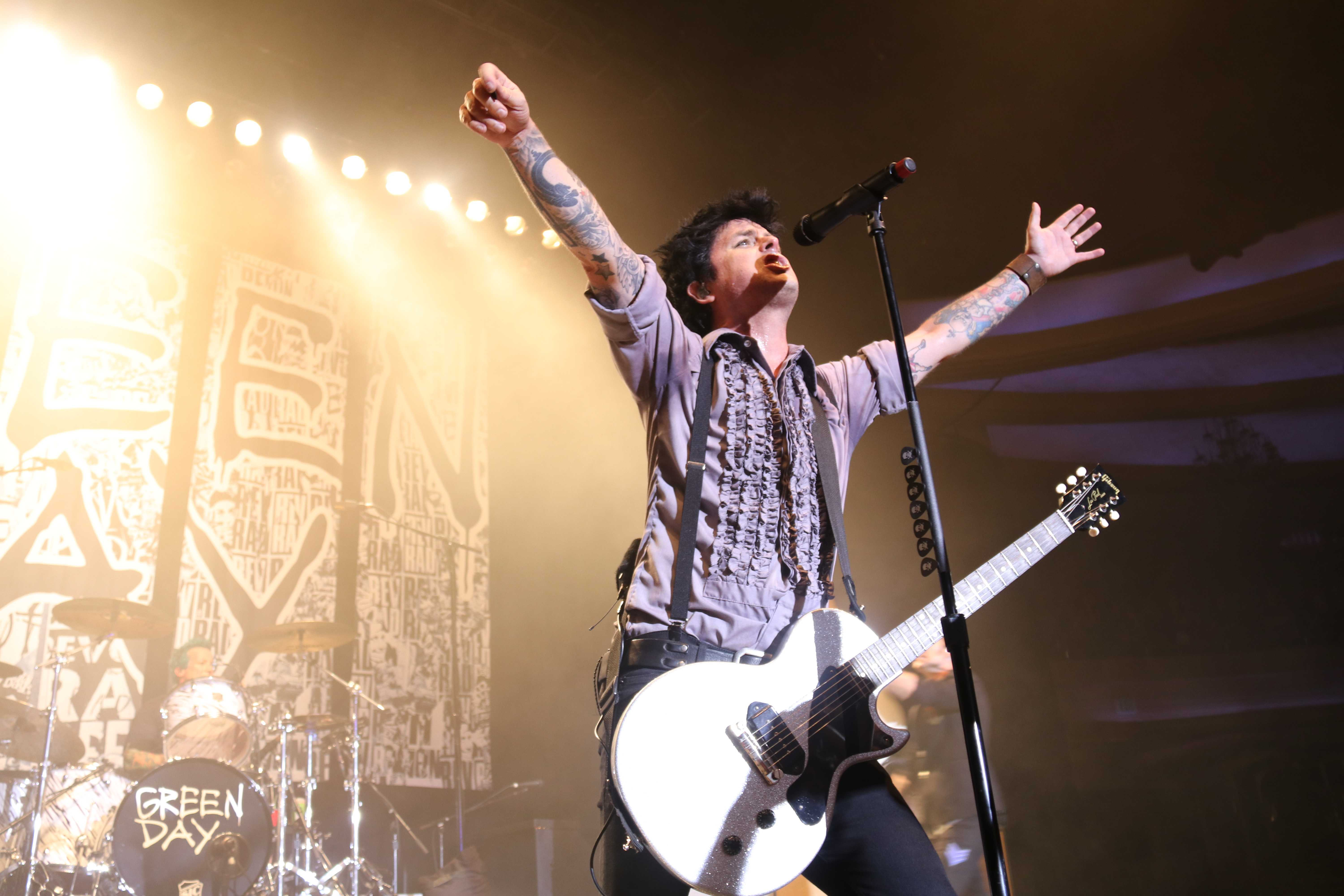 Billie Joe Armstrong raises his hands while performing a song