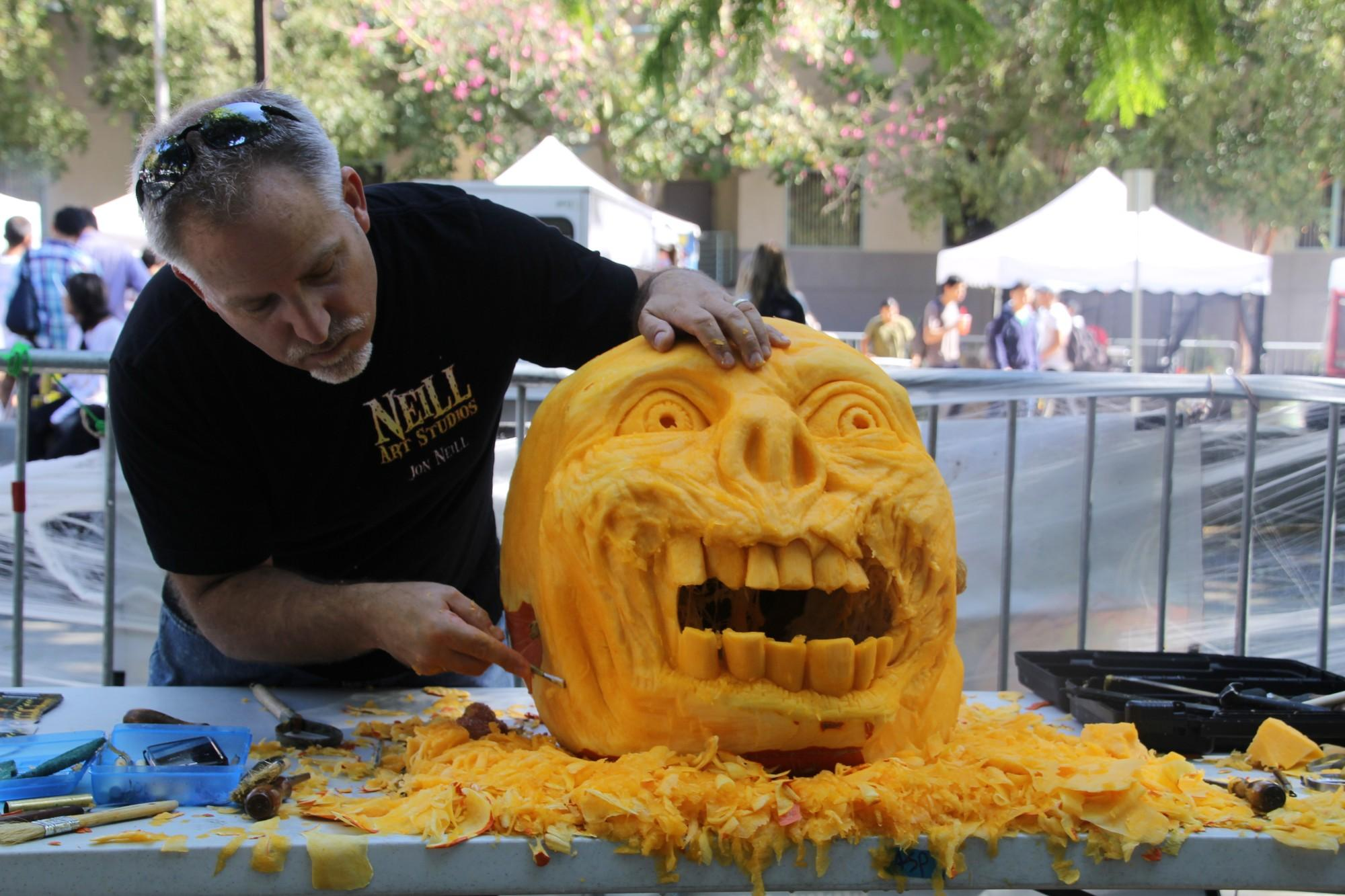 Man carves pumpkin in shape of a monster's face