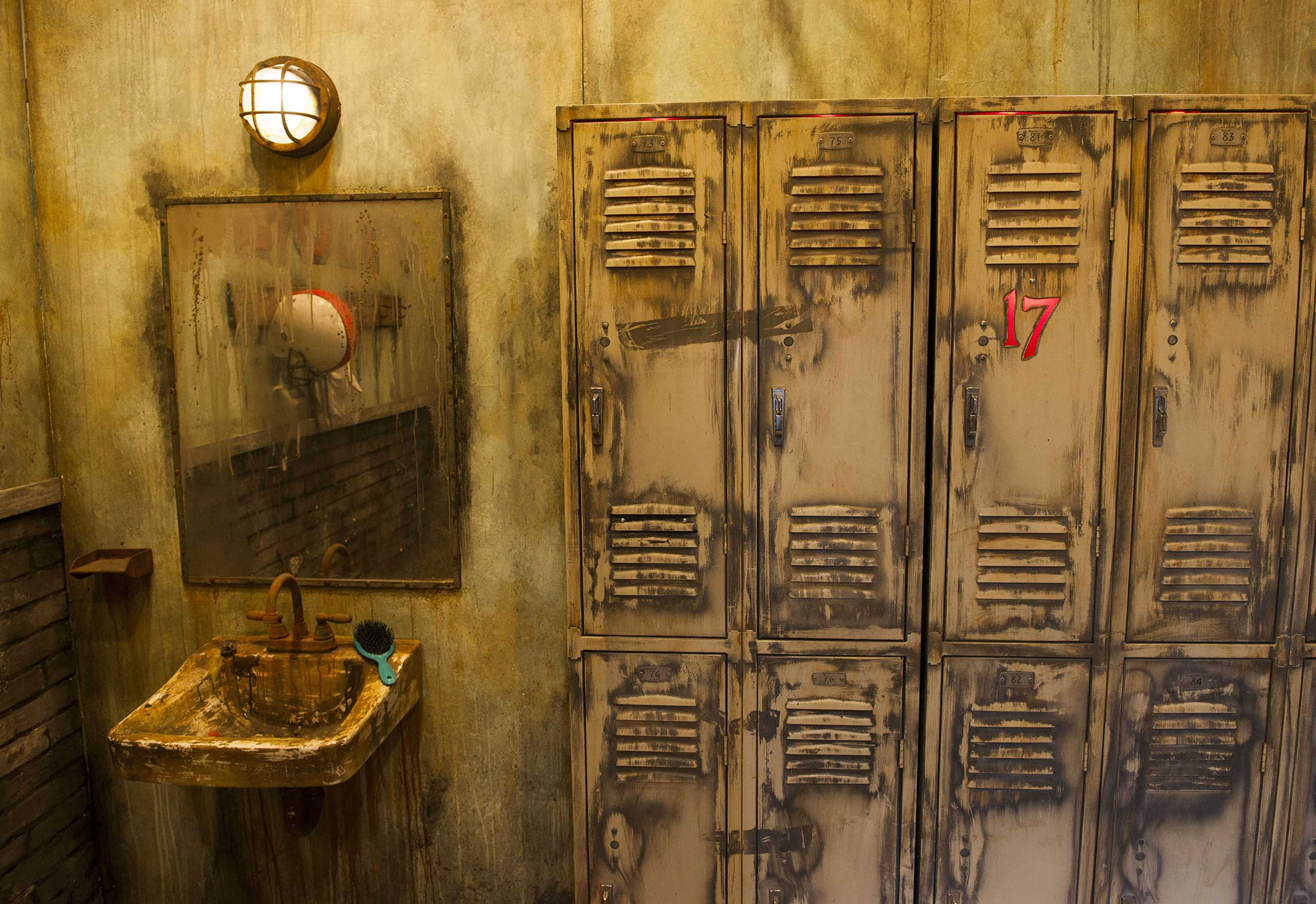 Inside of haunted house looks incredibly dirty with a muddy bathroom and some lockers that show a red number 17