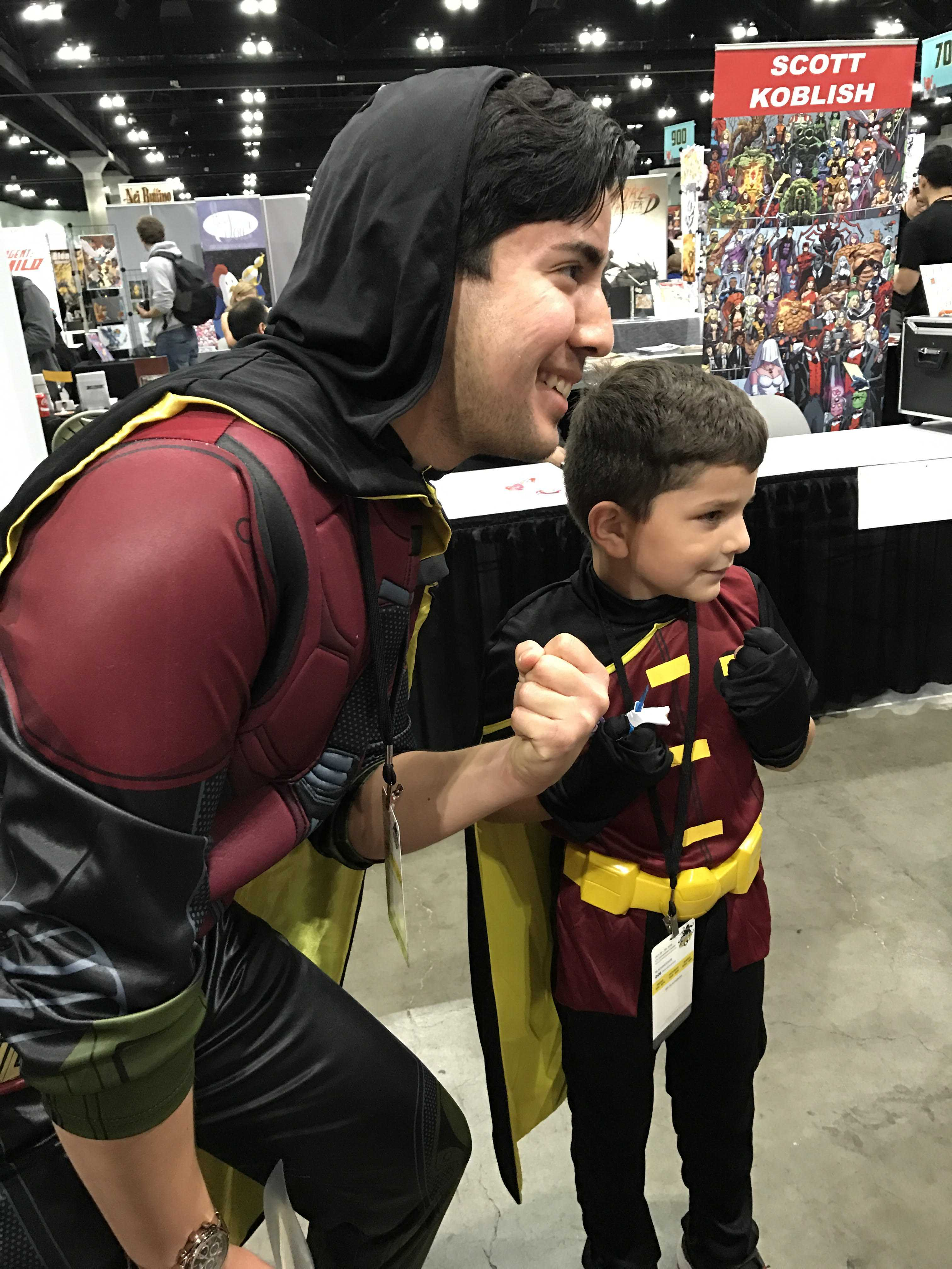A man dressed as Robin poses with a young boy in the same costume