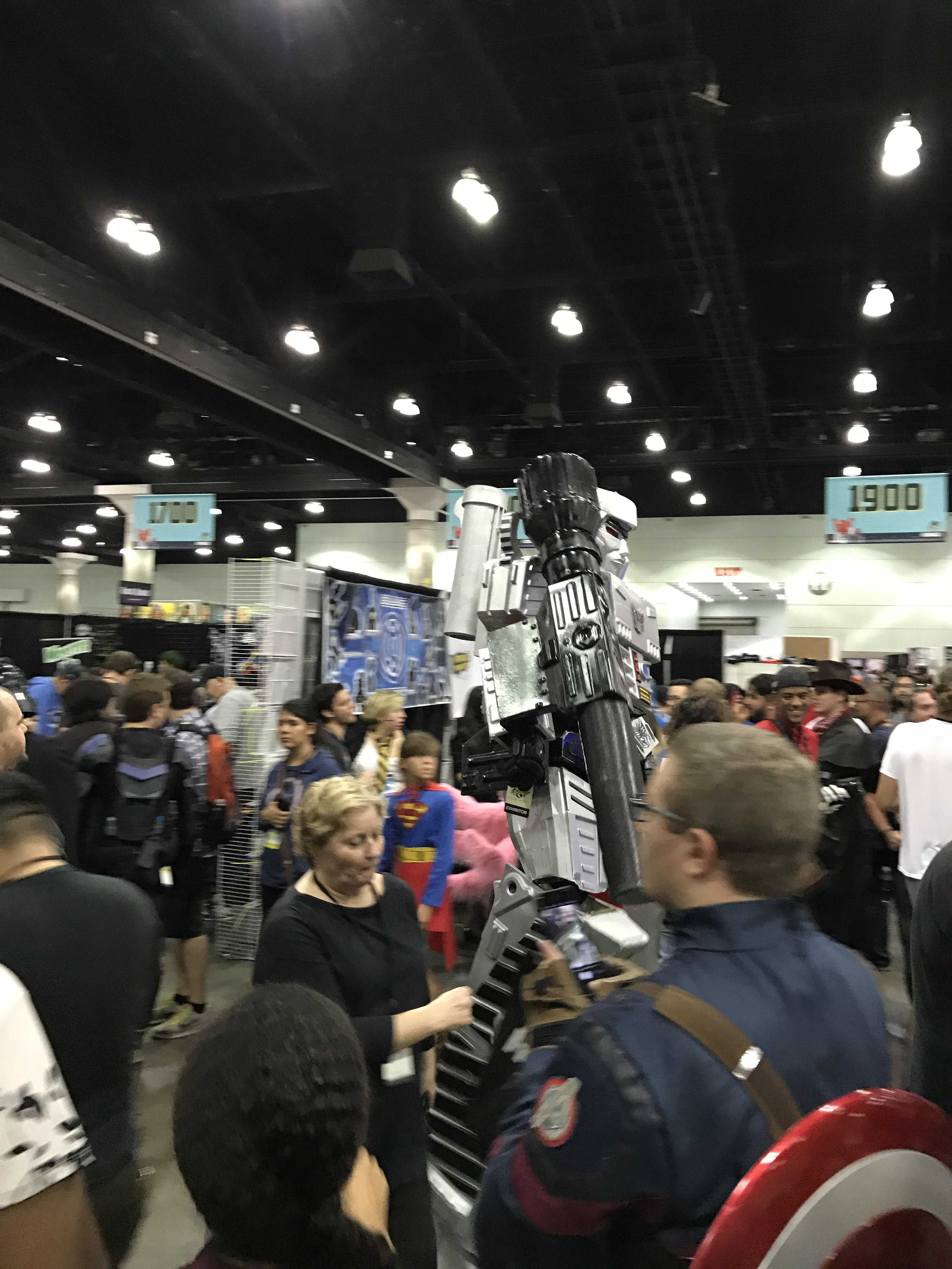 A large group of people gathers near the booths at comic con