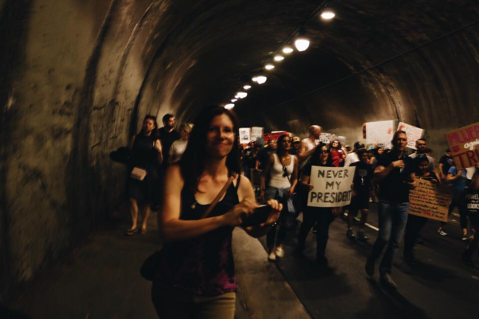 Various protesters march through dark tunnel
