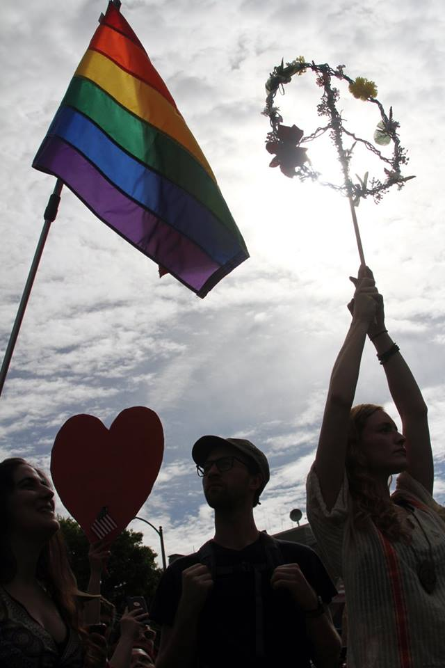 Protesters hold up the rainbow flag and a peace sign made of flowers