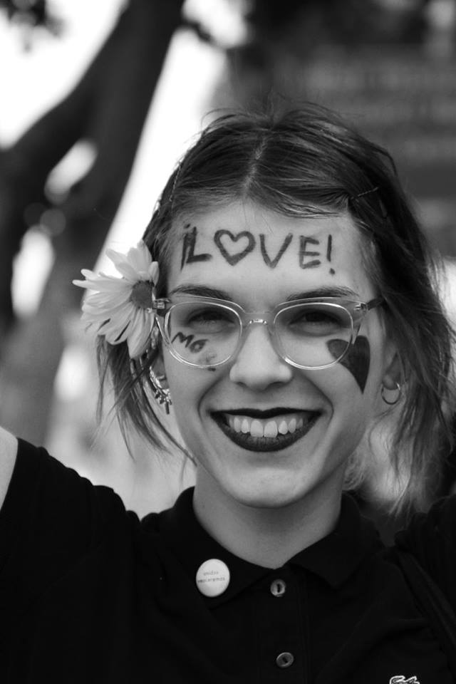 "Female protester is shown smiling with the word ""love"" written across her forehead"