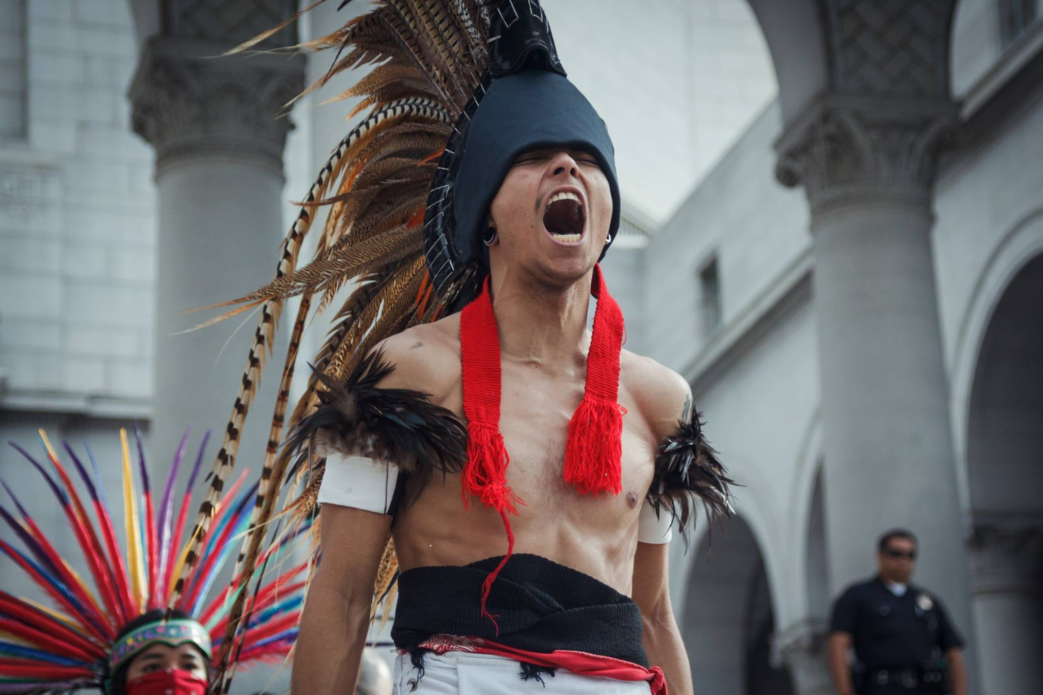 Man wearing a mohawk made of feathers is shown shouting