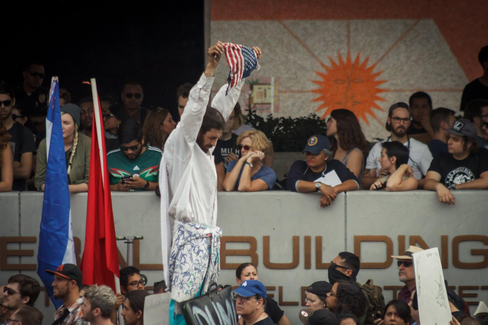 One man standing above a group of protesters holds up the American flag