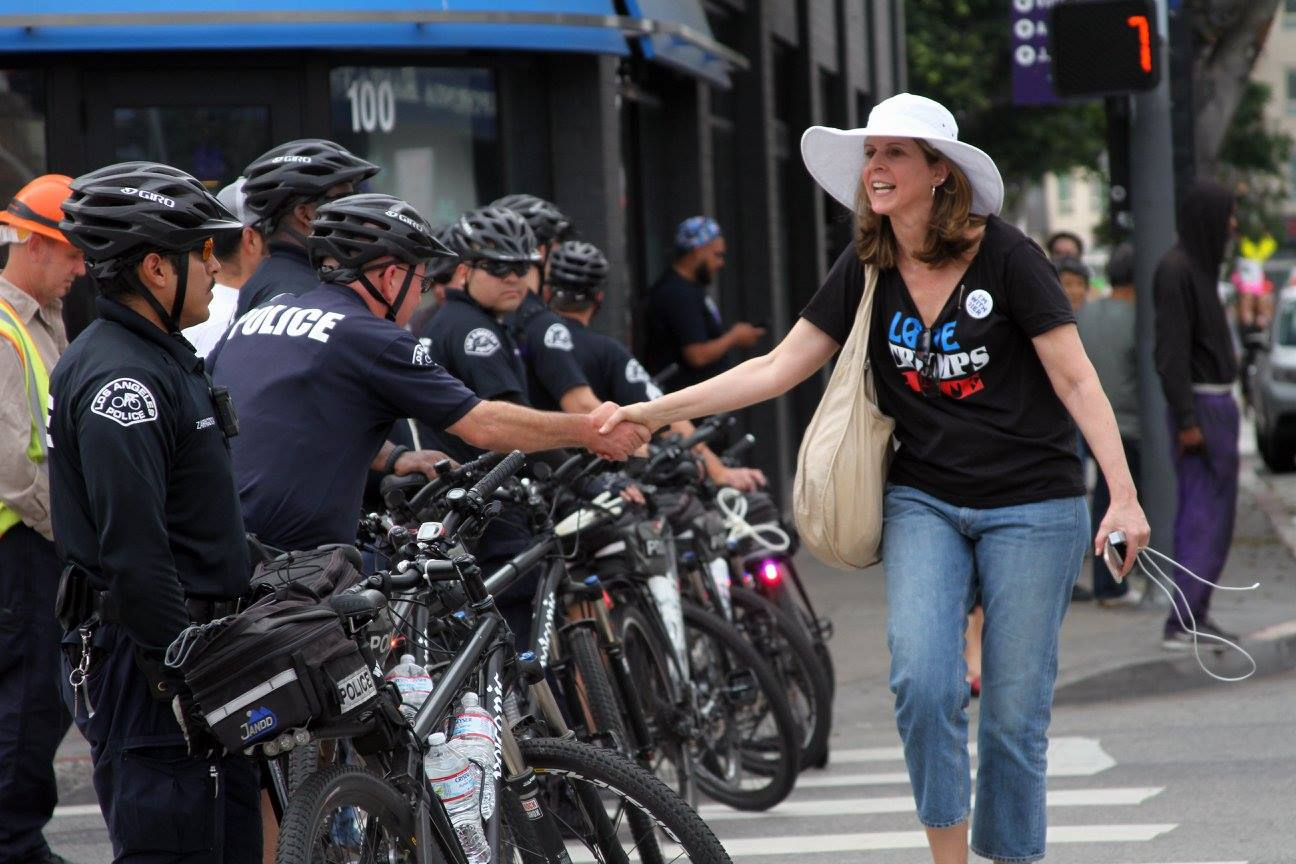 "Woman, whose shirt reads, ""Love trumps hate"", shakes hands with police officers"