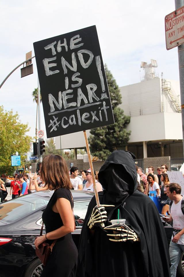 "Person dressed as grim reaper holds up sign which says, ""The end is near #calexit"""