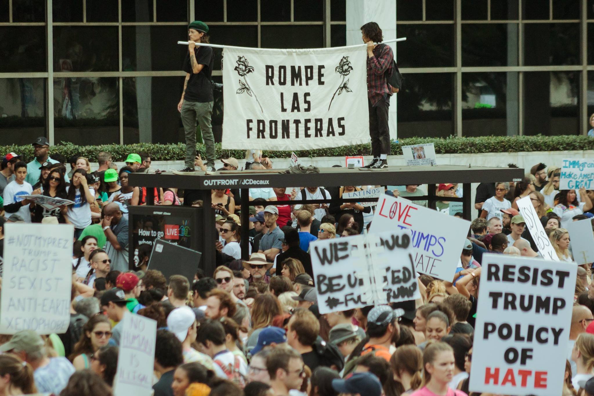 "Two people are shown standing above protesters with a banner that says, ""Rompe las fronteras"""