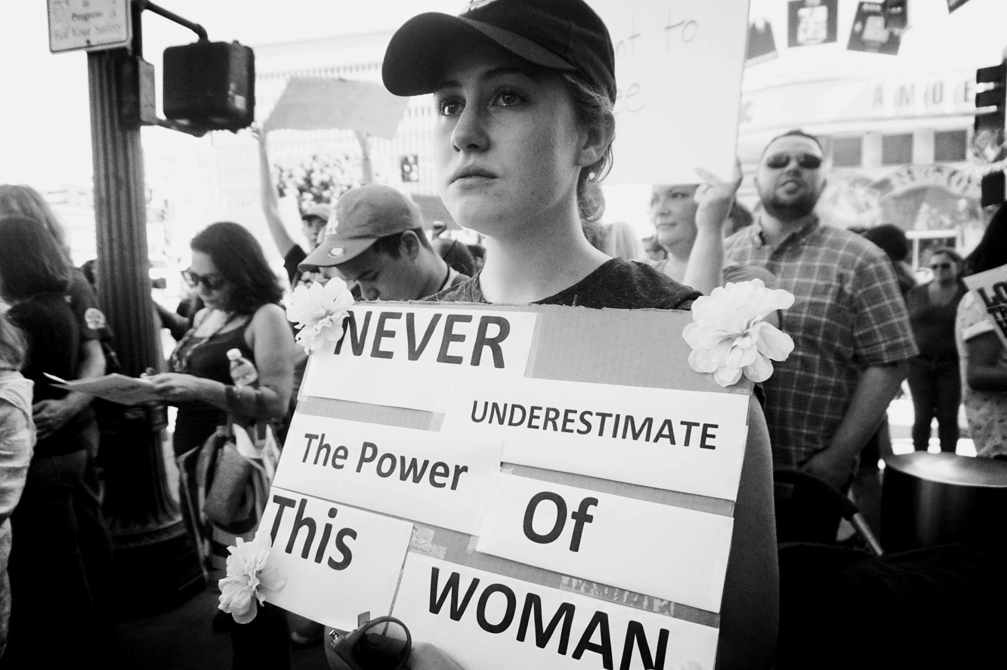 "Teary-eyed woman holds signs saying, ""Never underestimate the power of this woman"""