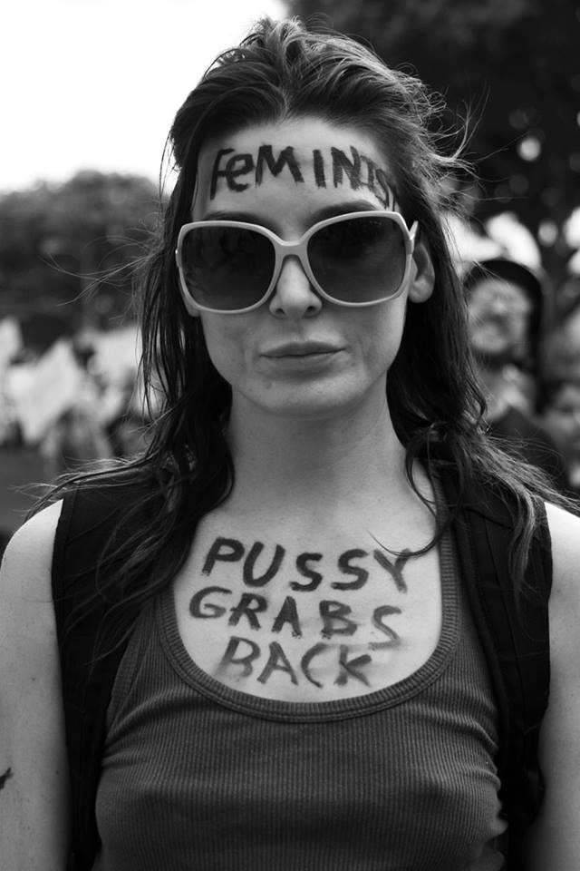 "Woman is shown with the word ""Feminist"" written on her forehead and the words, ""Pussy grabs back"" written along her chest"