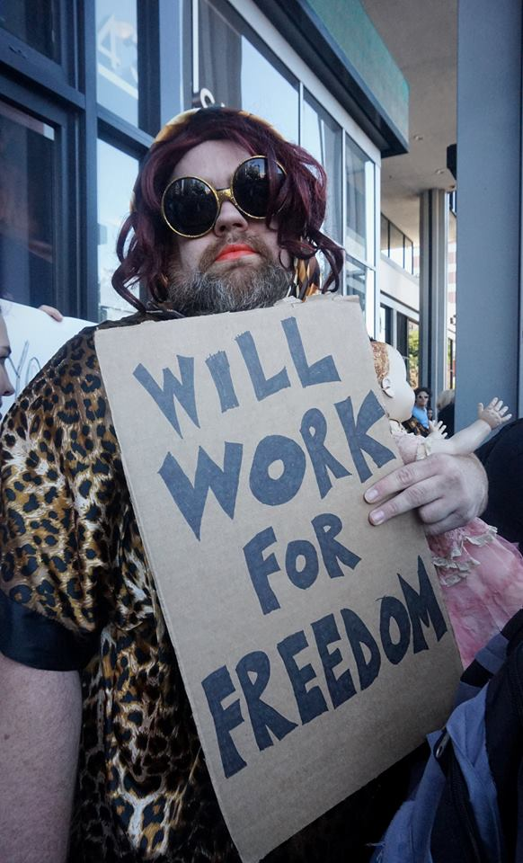 "Man dressed in drag holds sign that reads, ""will work for freedom"""