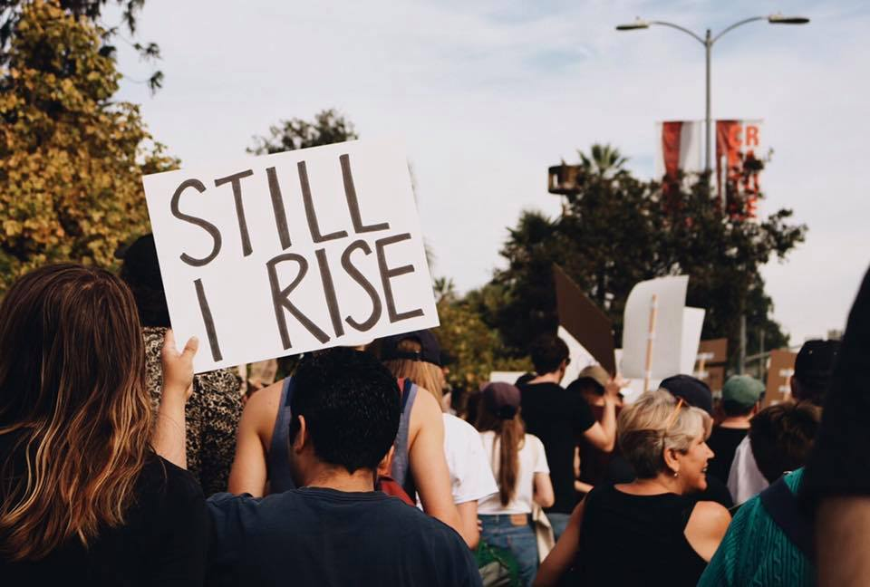 "Trump protesters march, one man holds a sign reading, ""Still I rise"""