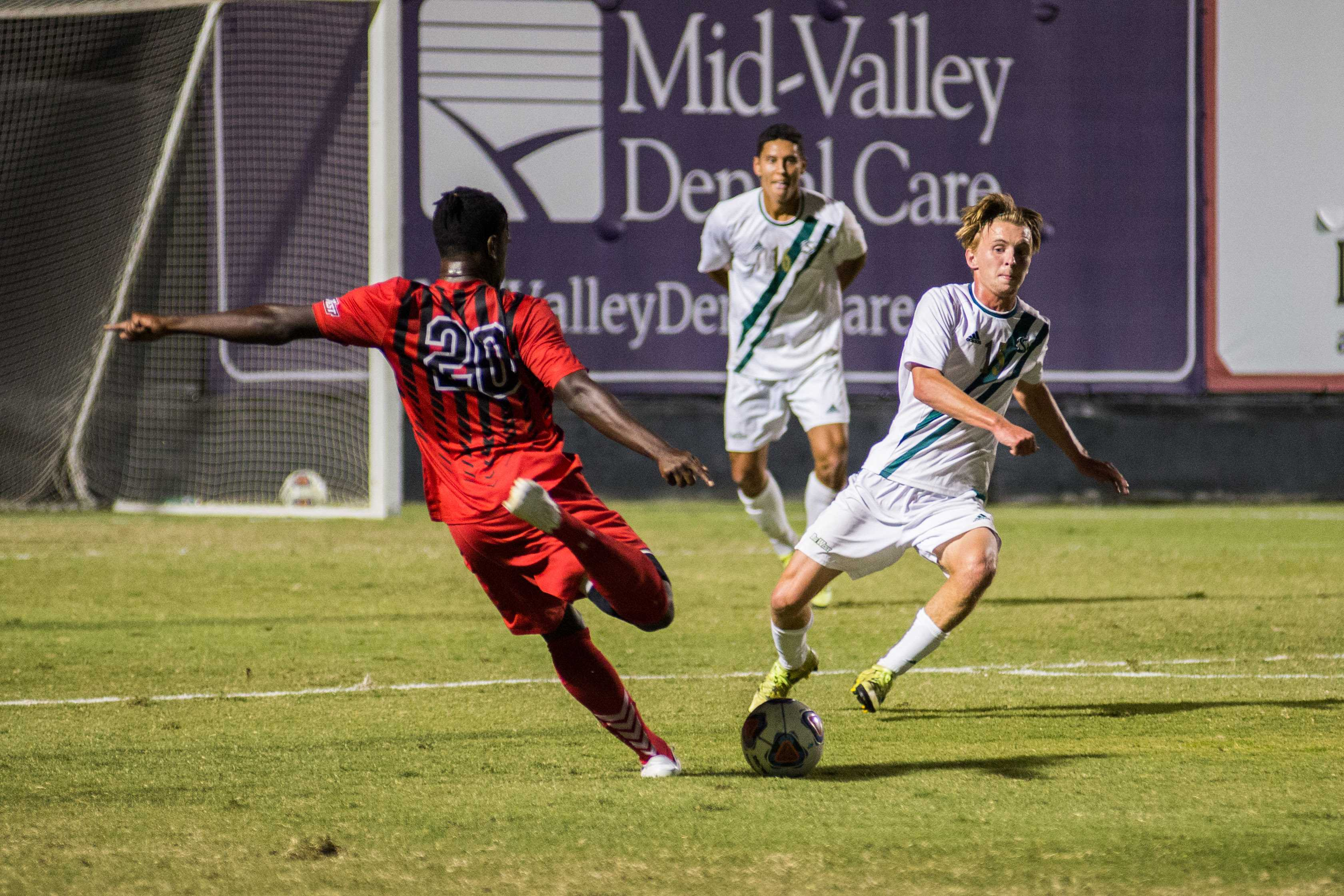 CSUN and CSUF player both race to kick the ball