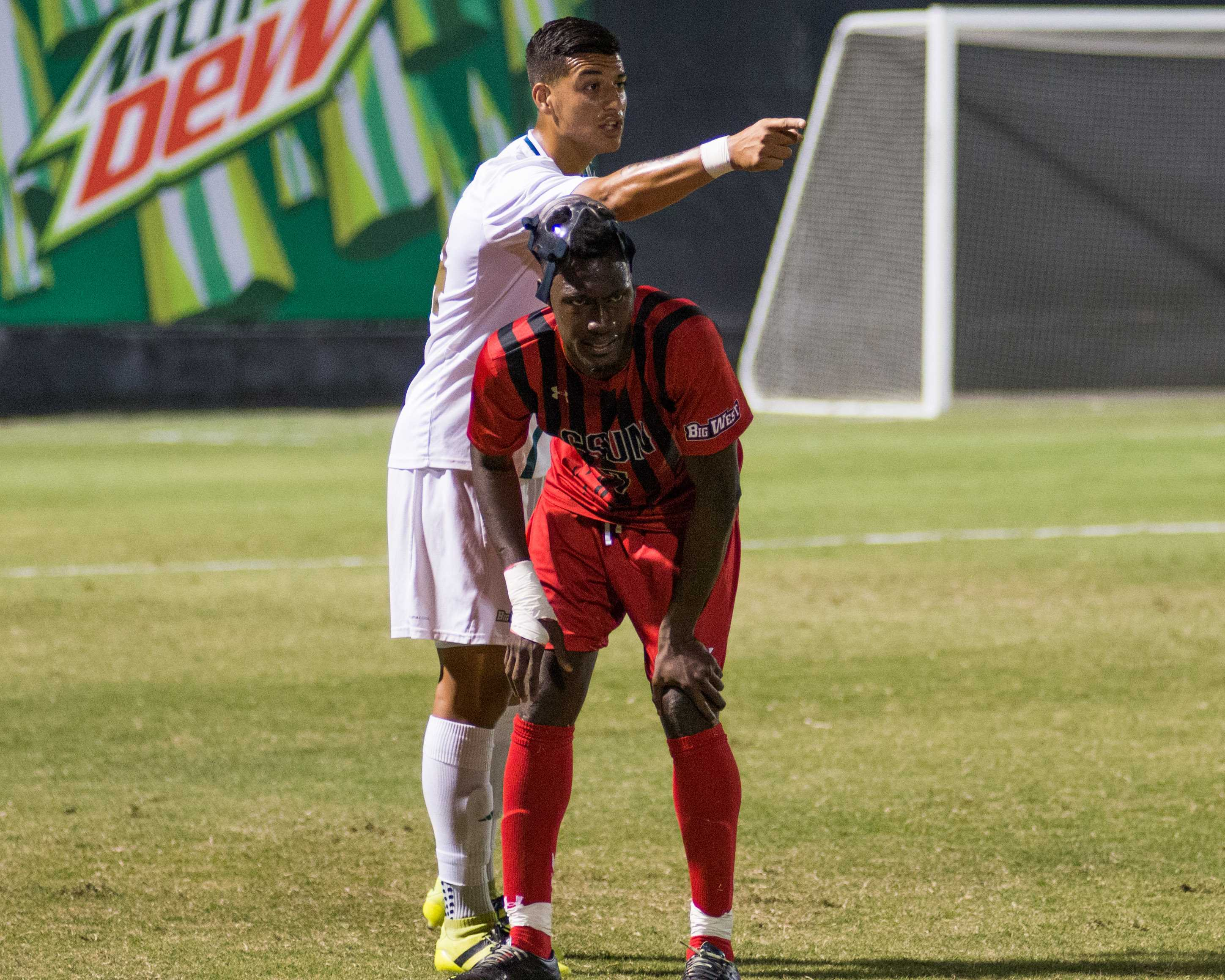 CSUF soccer player points while CSUN player is hunched over