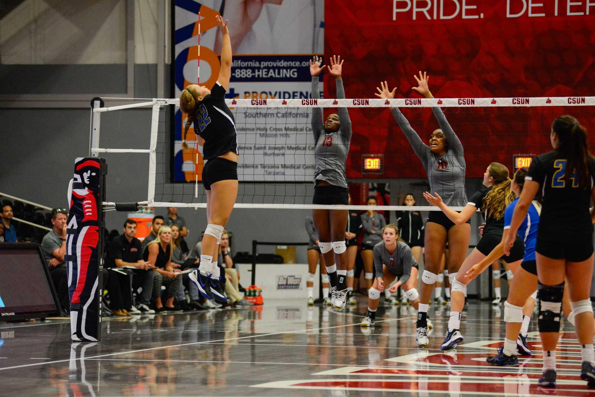 Volleyball players jump up and reach for the ball