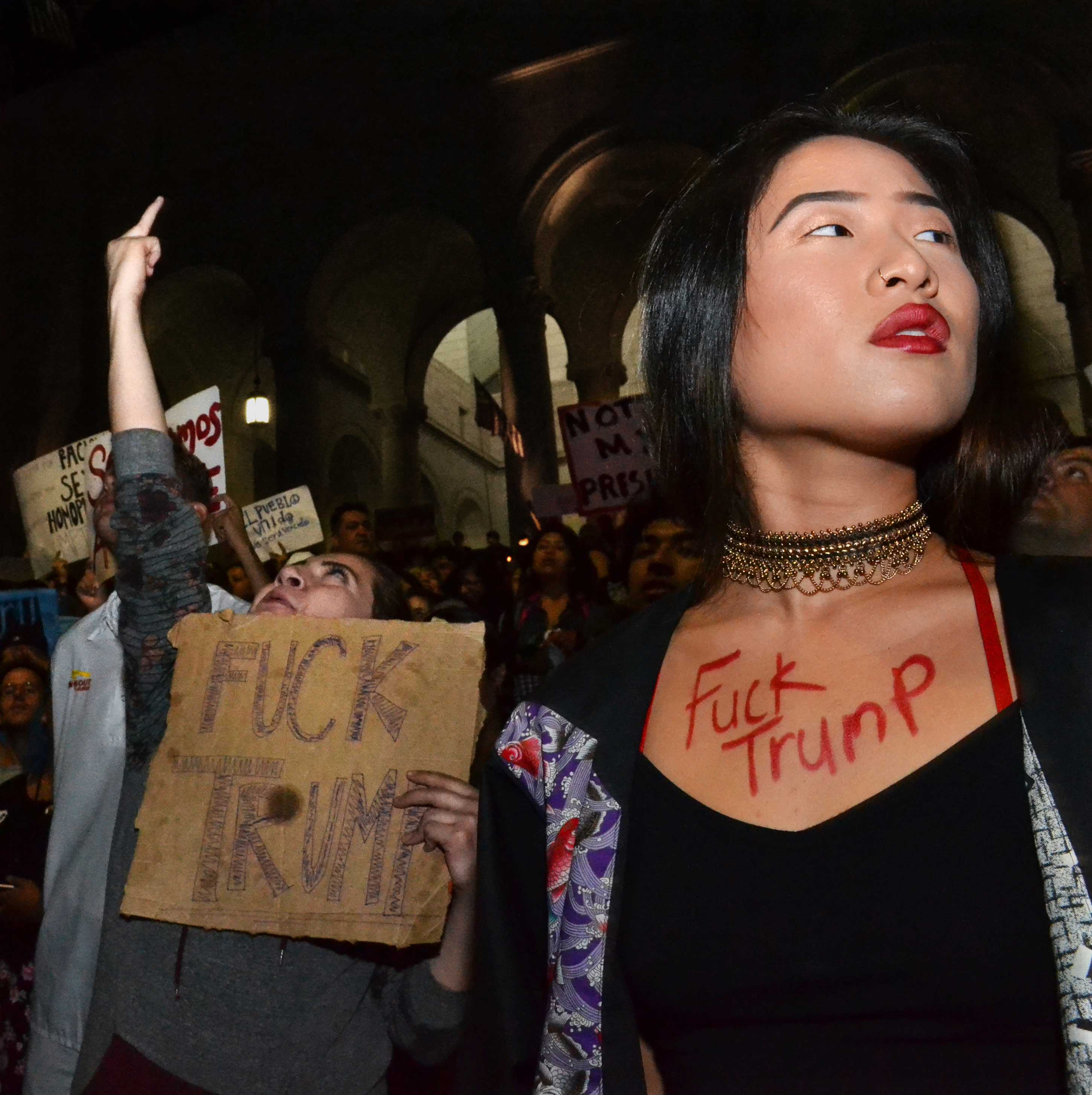 "Two women are shown with body art and signs reading ""Fuck Trump"""