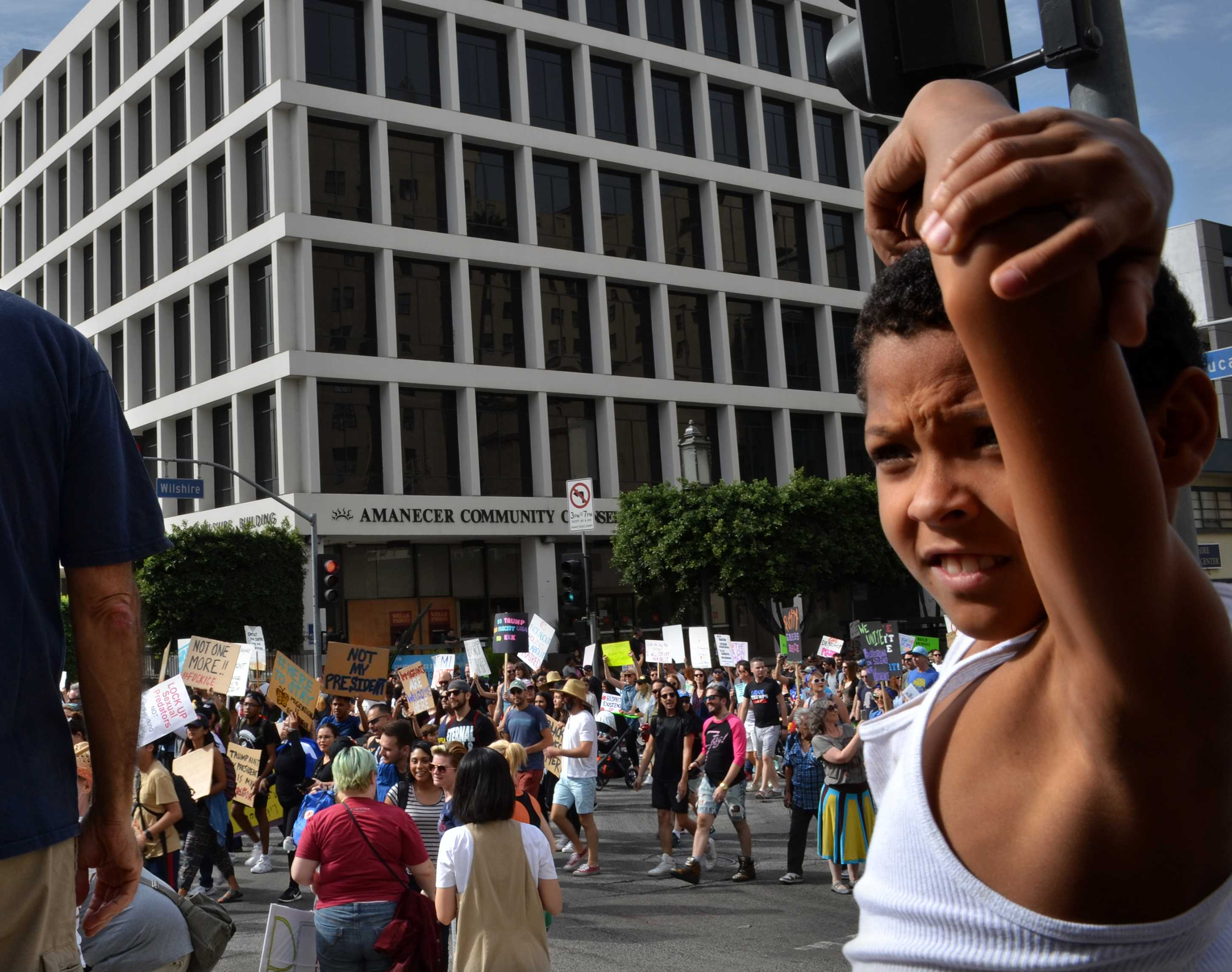 Child is shown next to large group of protesters