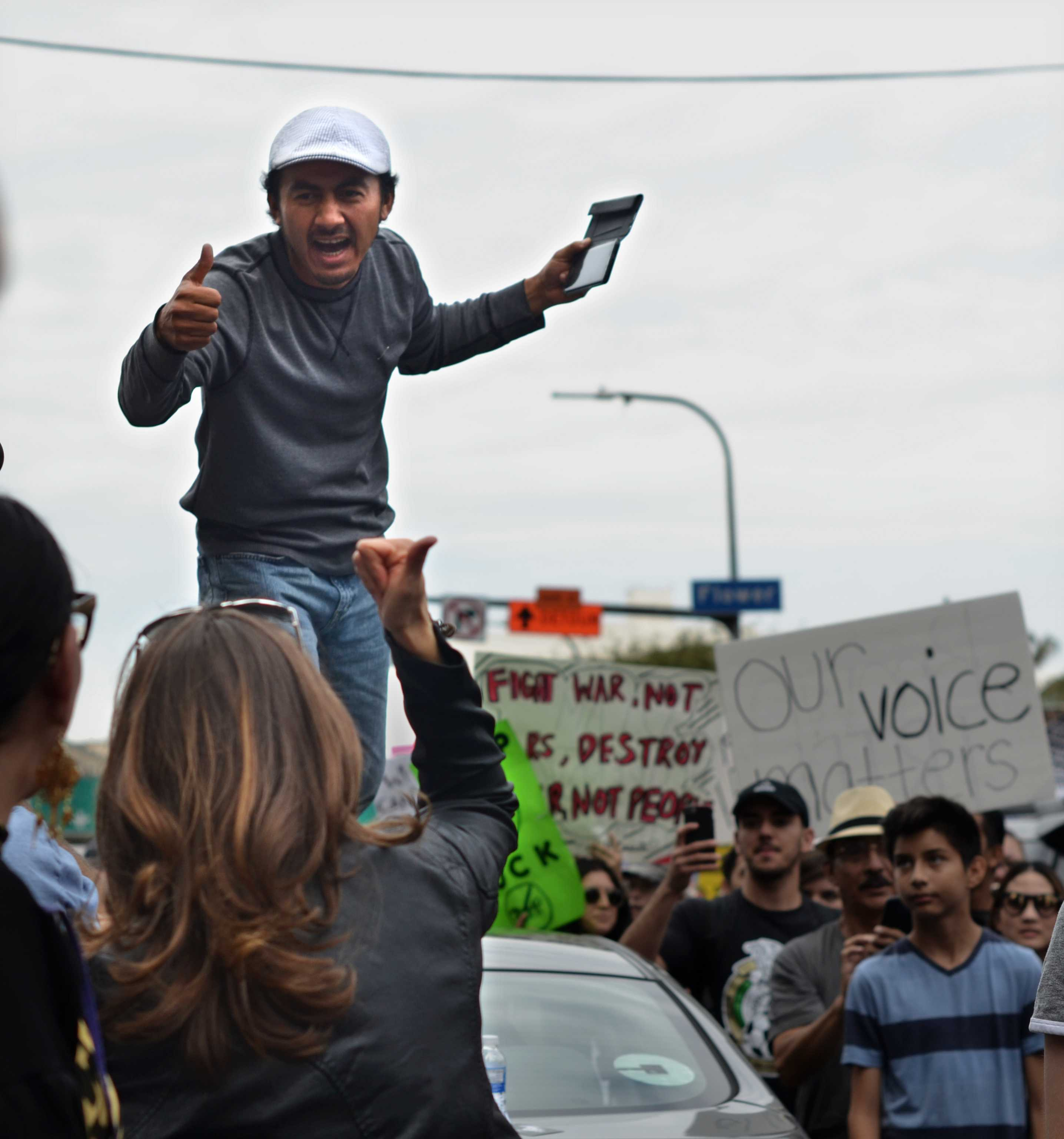 Man stands on top of car and cheers with anti-Trump protesters
