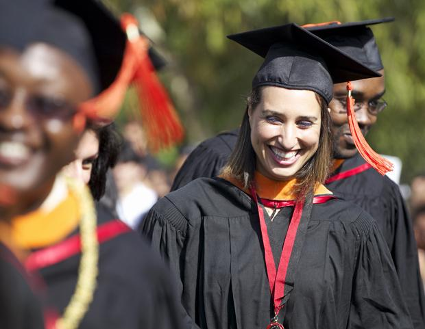 Three students shown smiling on graduation day in cap and gown