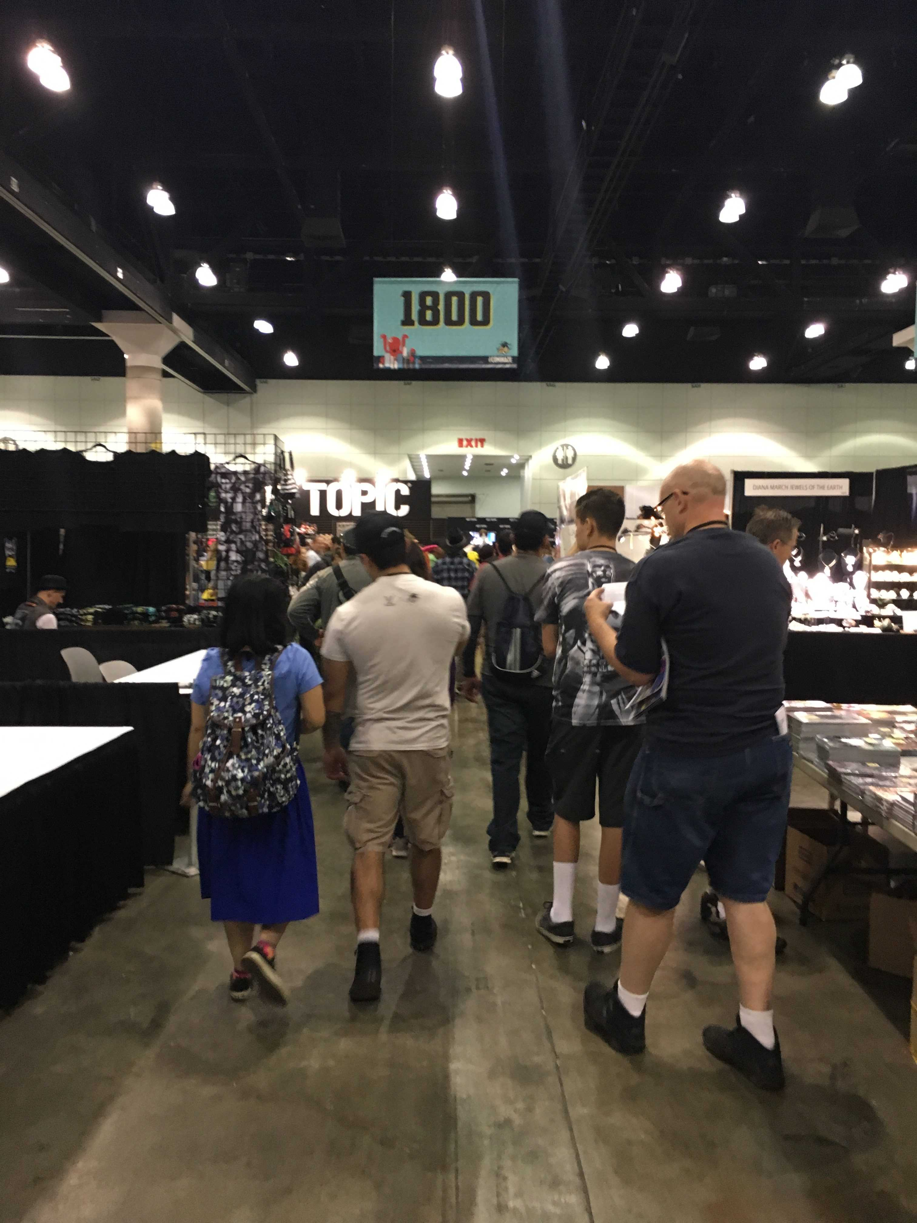 People walk through the booths at comic con