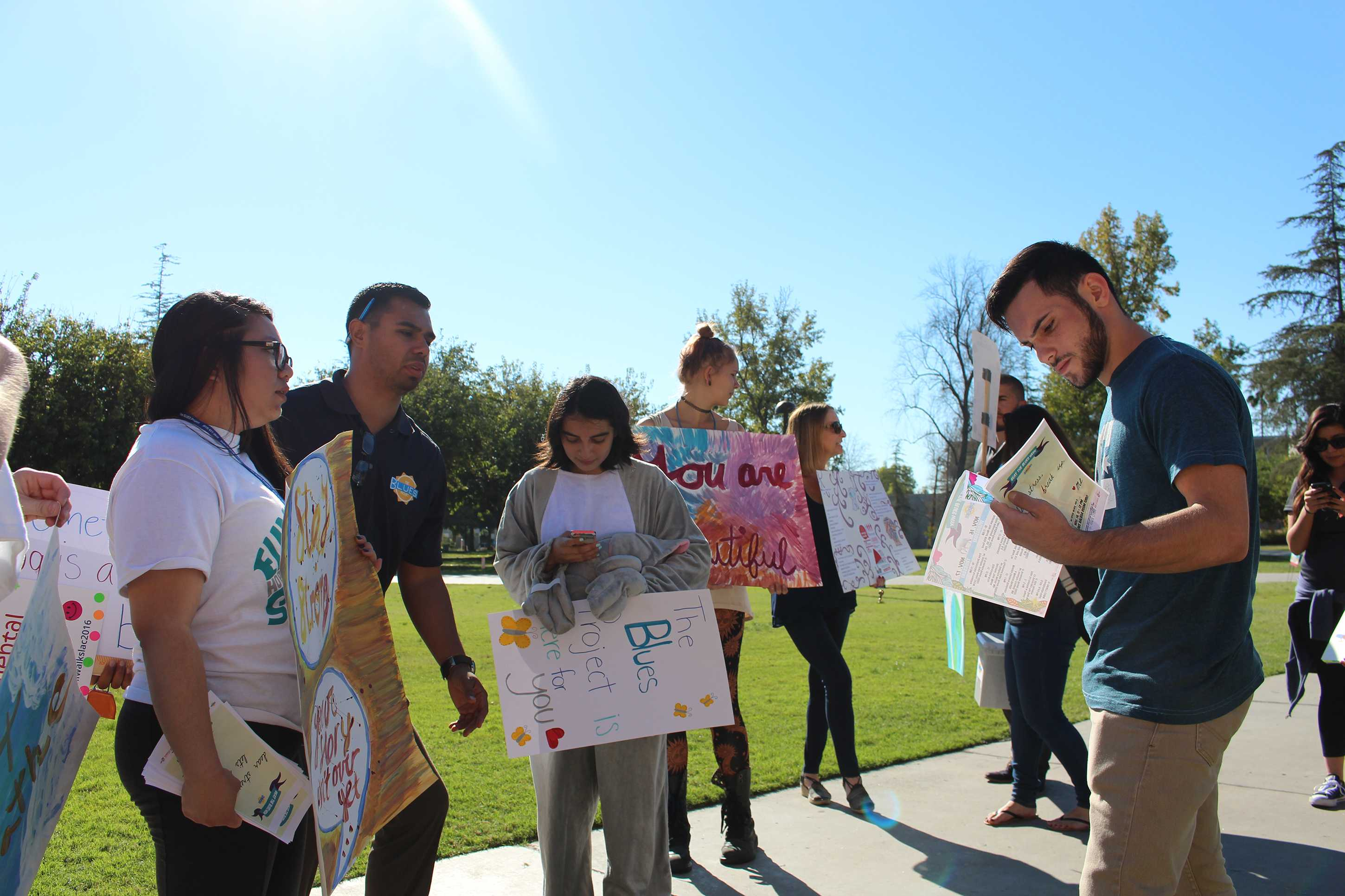 A group of people with posters discuss mental health with a CSUN student