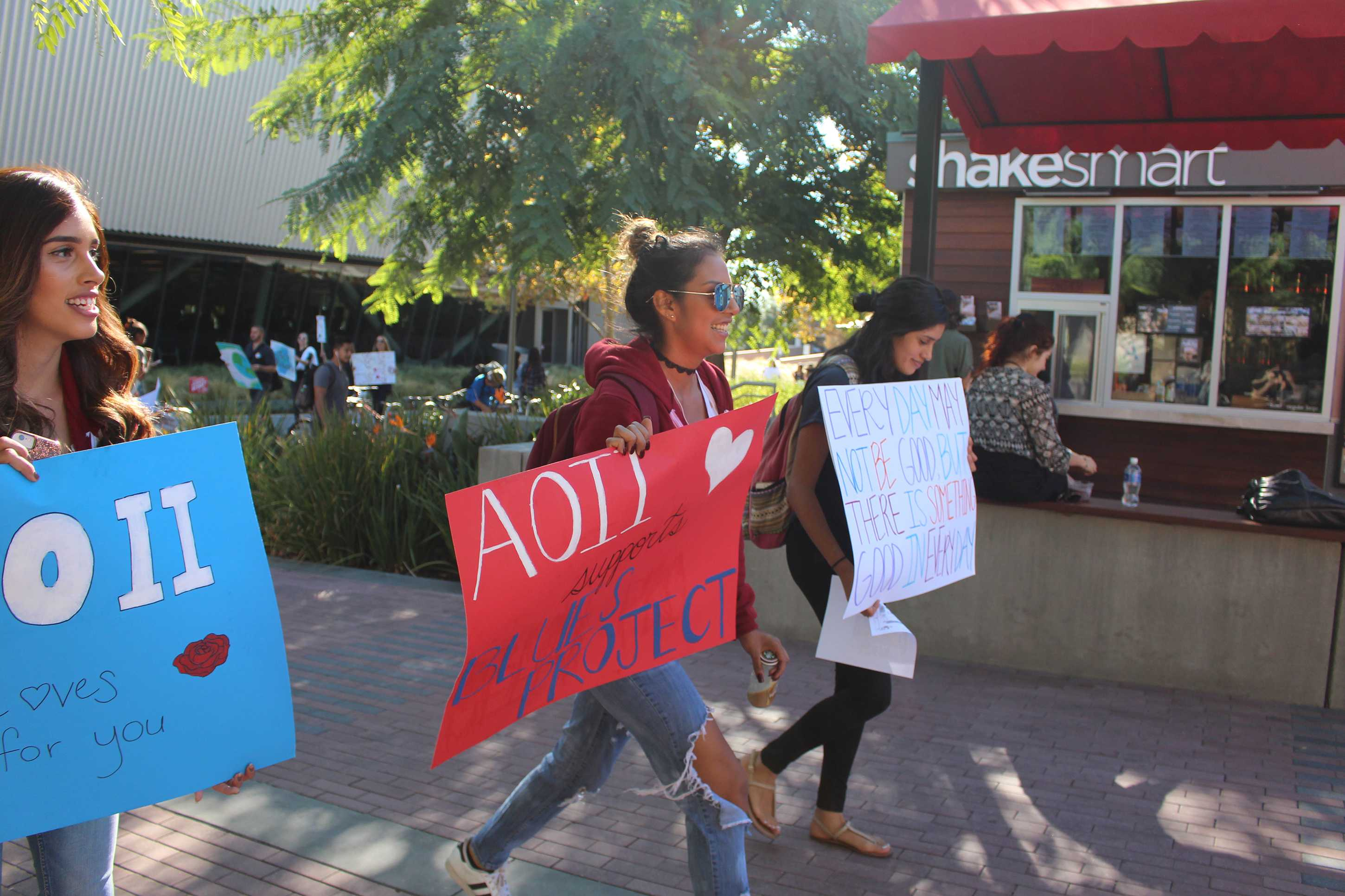 Sorority members carry signs in support of the Blue's Project
