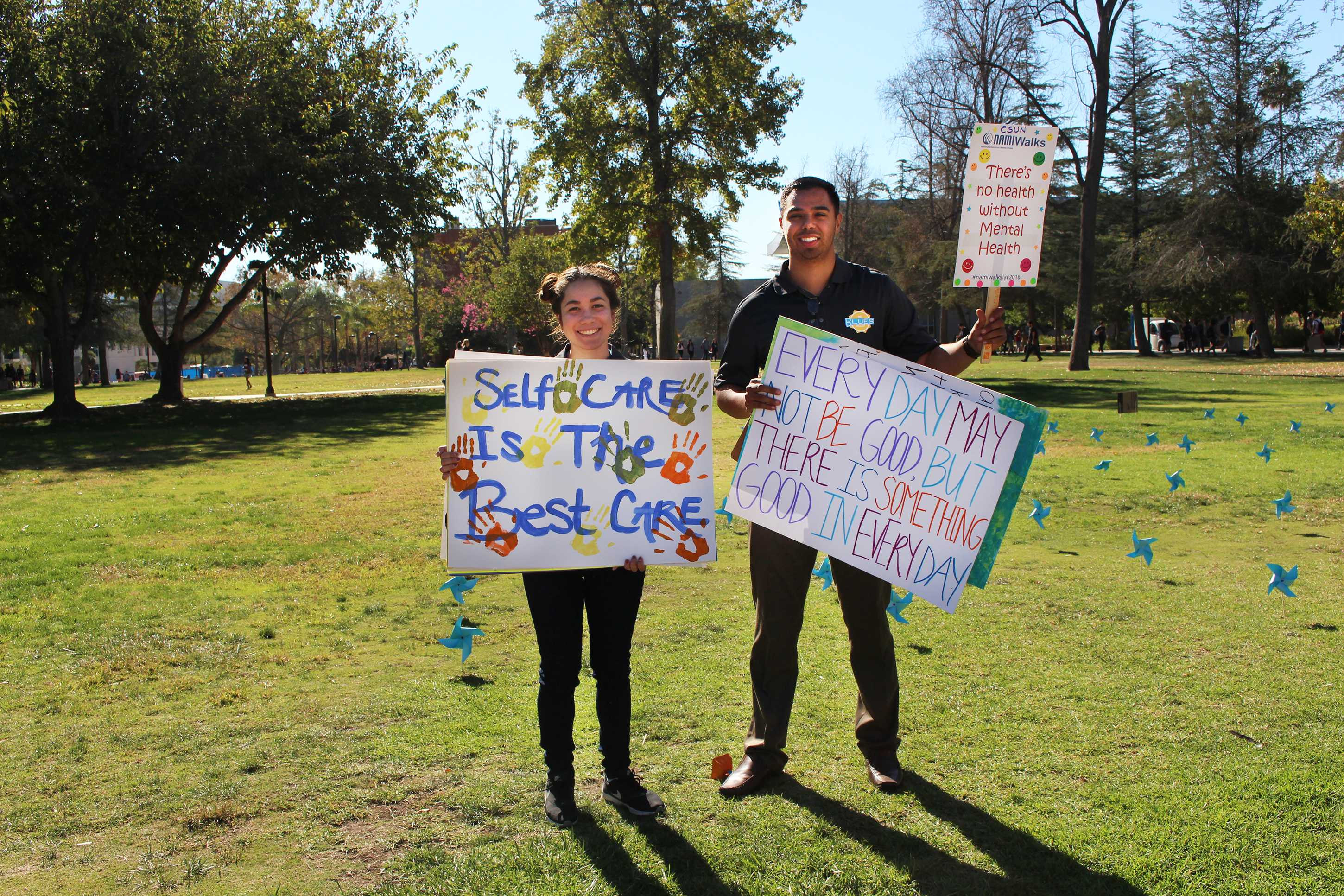 Two students hold up signs with positive messages