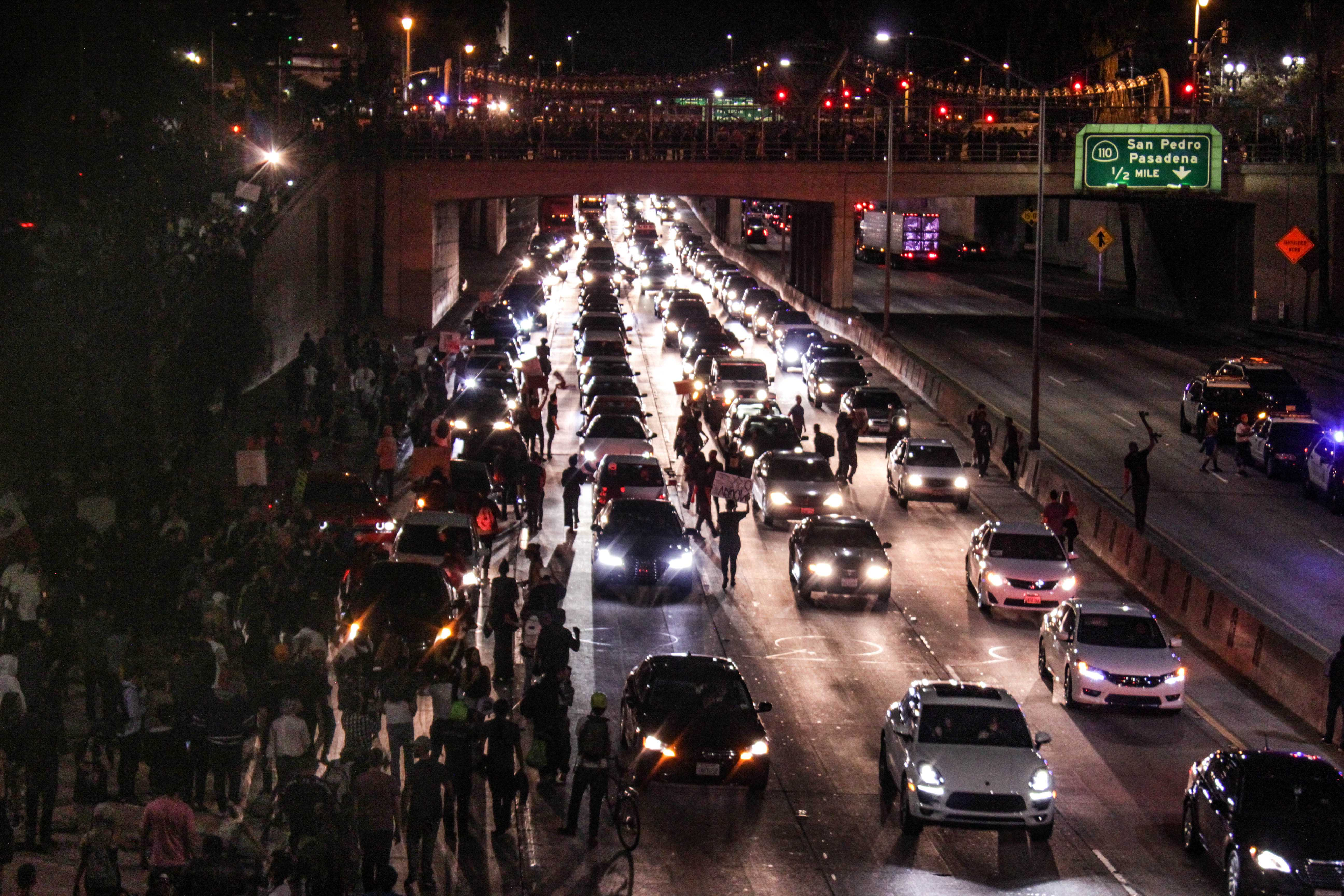 Picture shows protesters blocking several lanes of the freeway