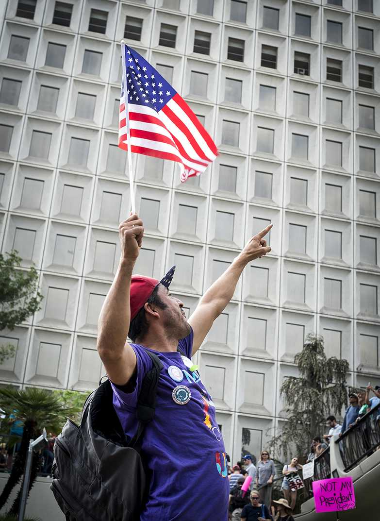 Protester points up and waves American flag