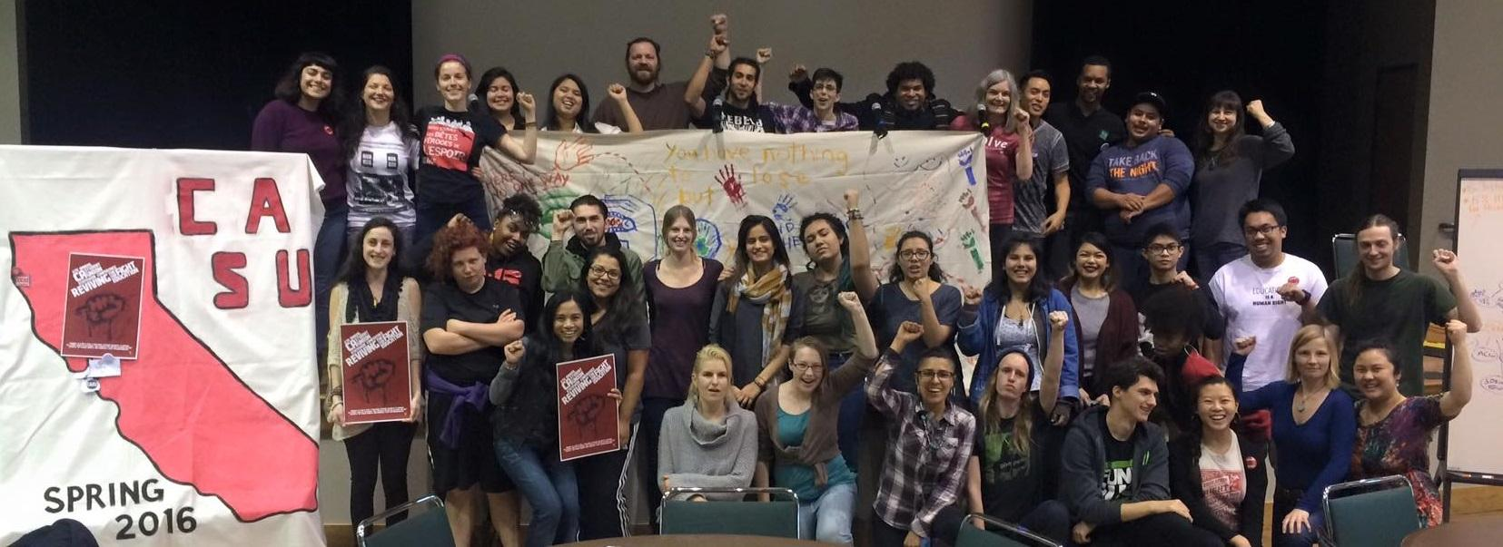 a large group of members of the student union pose with a large banner