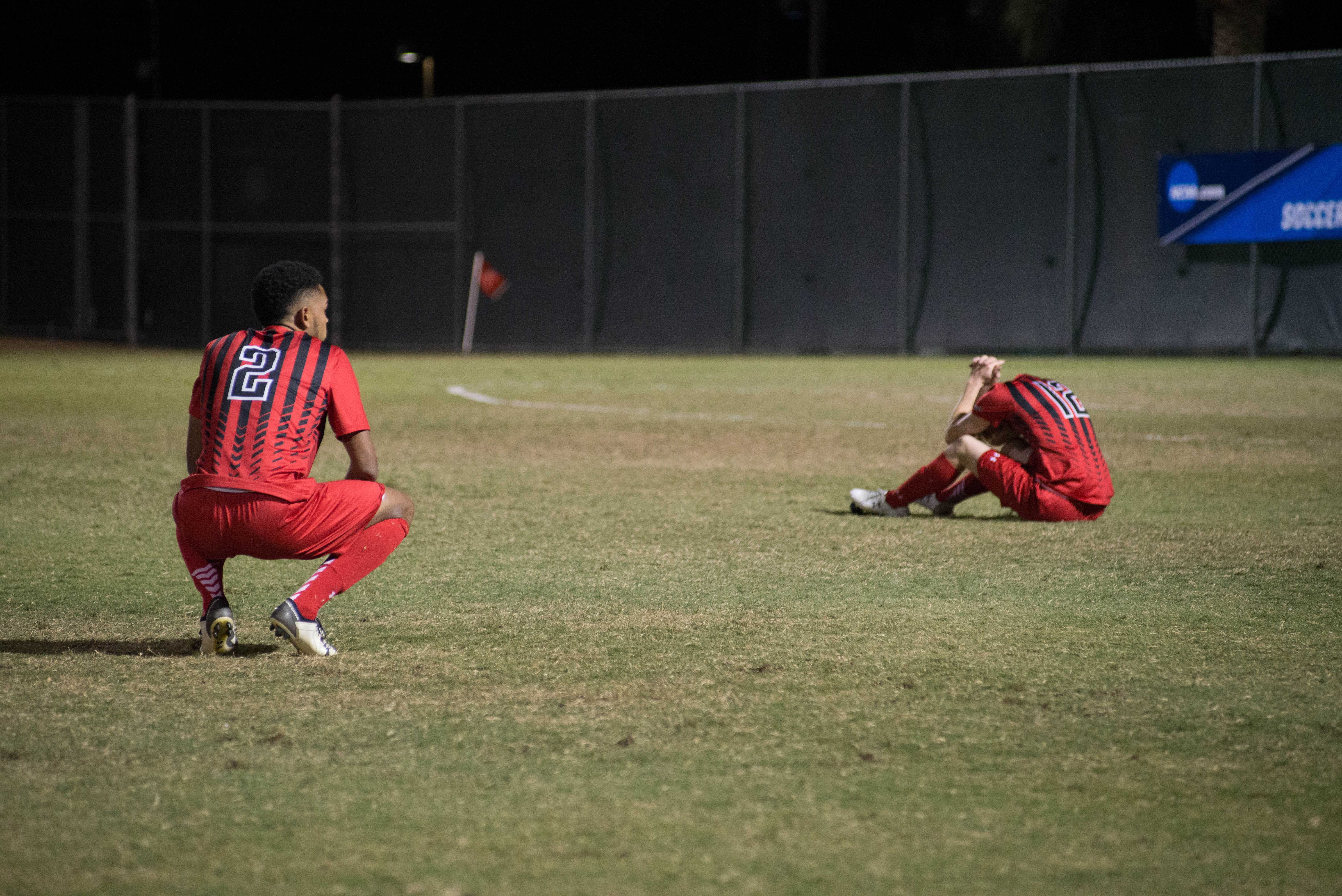 CSUN soccer players sit on the field