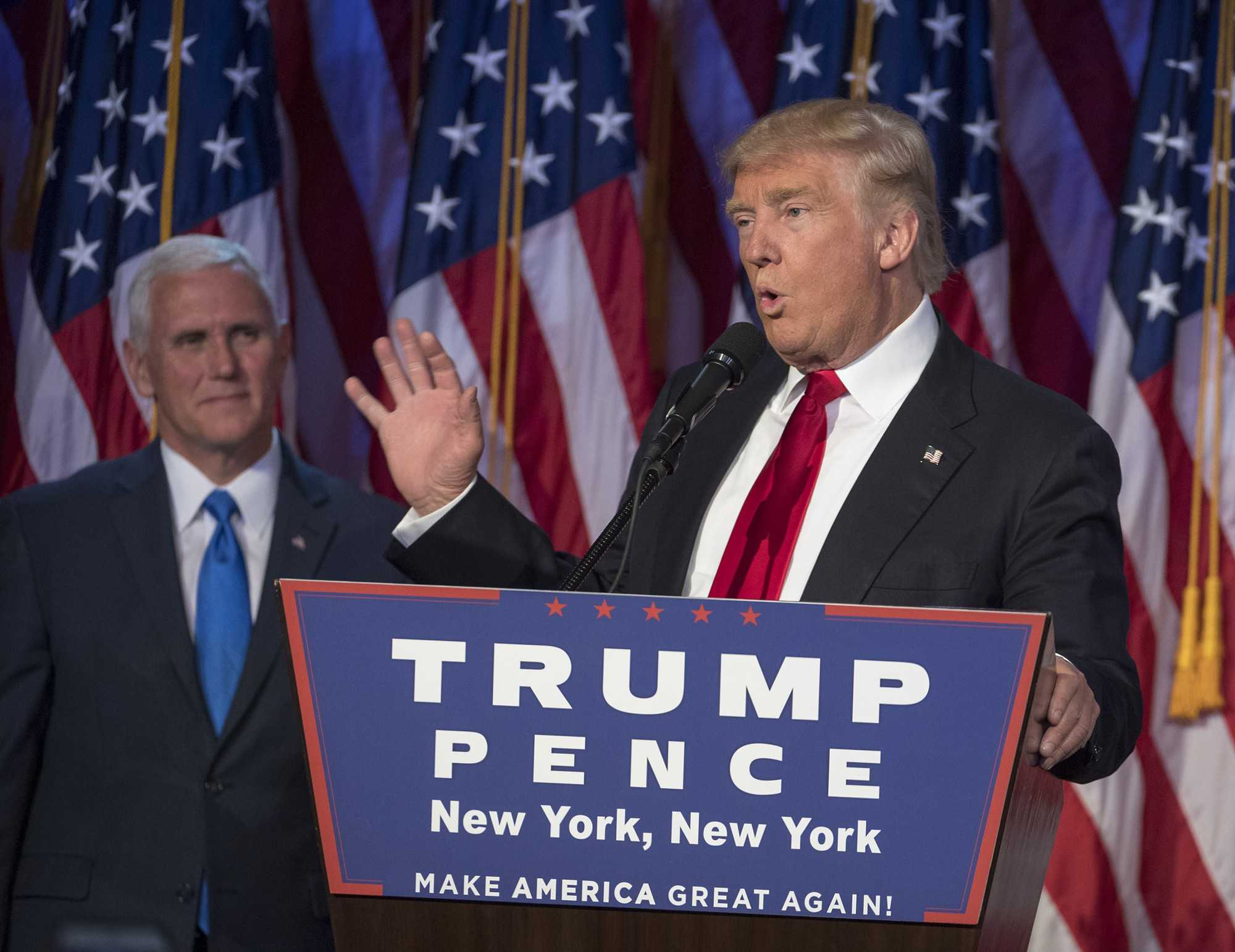 Trump shown speaking on the podium next to running mate Mike Pence