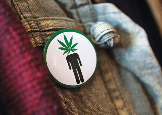 Picture shows pin with a cartoon person with a Marijuana leaf for a head