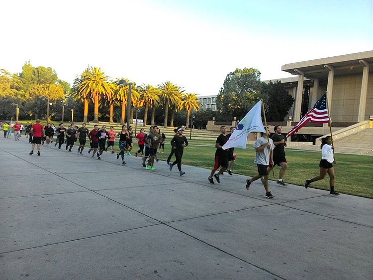 CSUN+students+pictured+running+in+front+of+the+Oviatt+Library+waving+flags