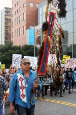 People in the streets protest the Dakota Access Pipeline with Native American cultural symbols and posters