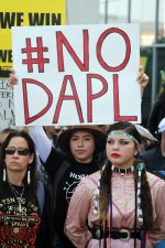 "Woman at protest holds sign that says, ""# no D.A.P.L."""