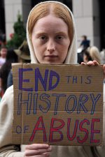"Woman holds sign that says, ""end this history of abuse"""