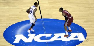 Tharpe dribbles the ball in the center of the court as Walden covers him