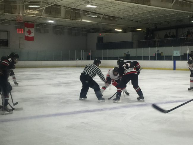 CSUN player and opposing team member wait for the referee to drop the puck