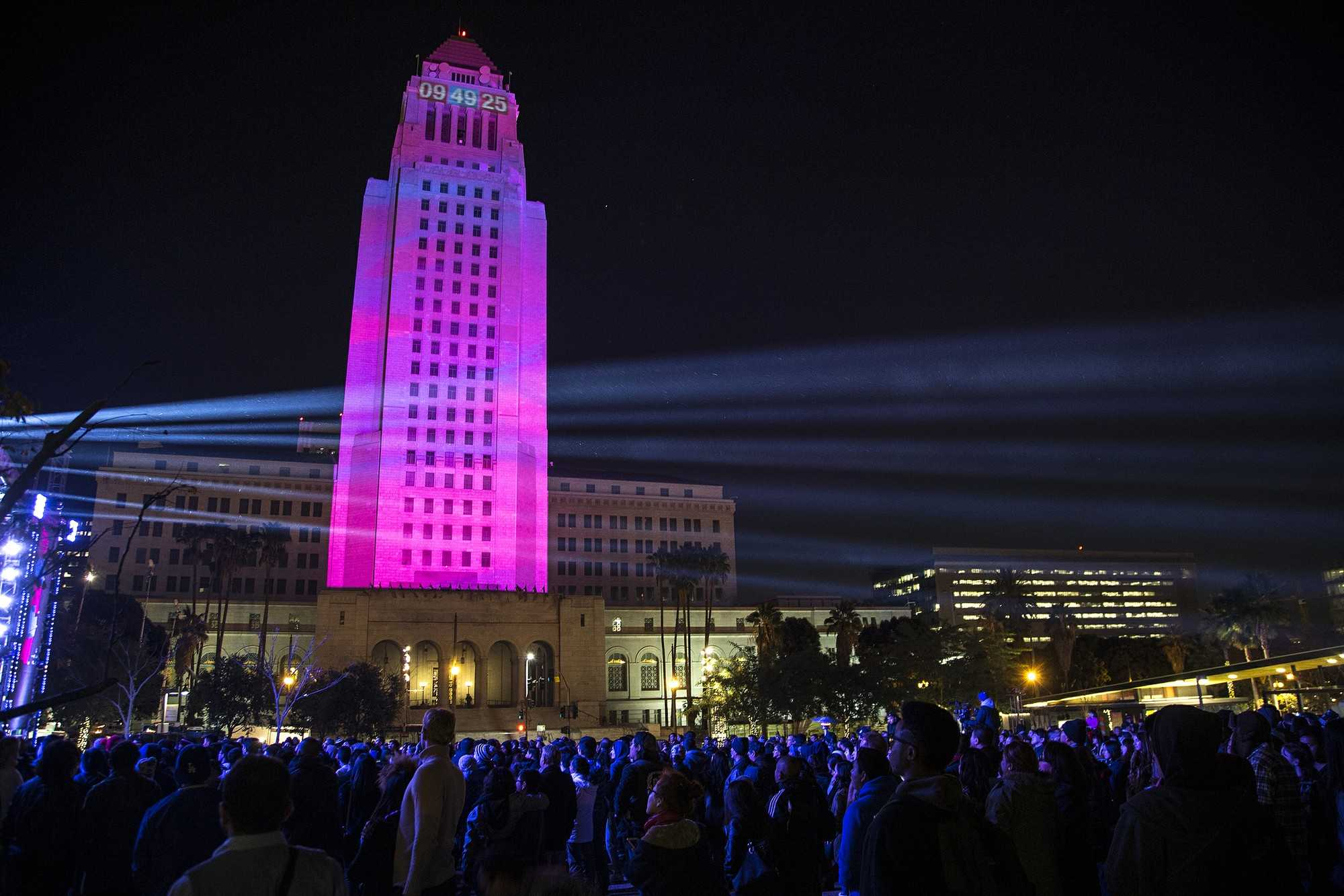 Los Angeles City Hall is lit up in pink with the countdown clock illuminated at the top as revelers enjoy live music  during New Year's Eve celebration at Grand Park in Los Angeles on December 31, 2015. (Gina Ferazzi/Los Angeles Times/TNS)