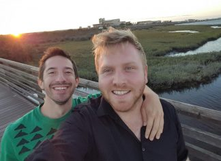 Two men pictured in front of a lake